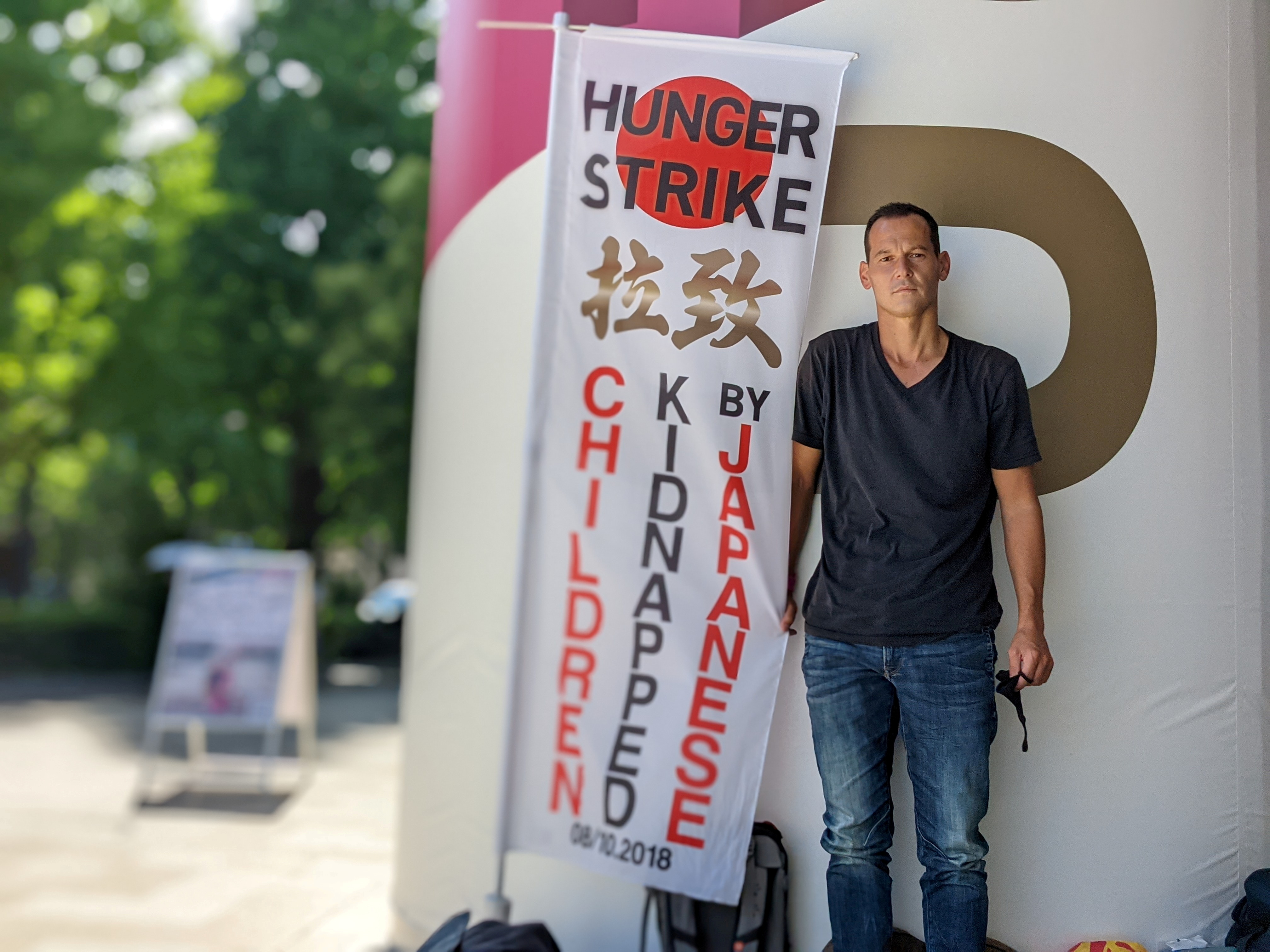 French father-of-two Vincent Fichot stands with his banner where he has been on a hunger strike since July 10 to protest what he says is Japan's sanctioning of child 'abductions' by a parent, near the Olympic Stadium in Tokyo, Japan July 21, 2021.  REUTERS/Chang-Ran Kim/File Photo