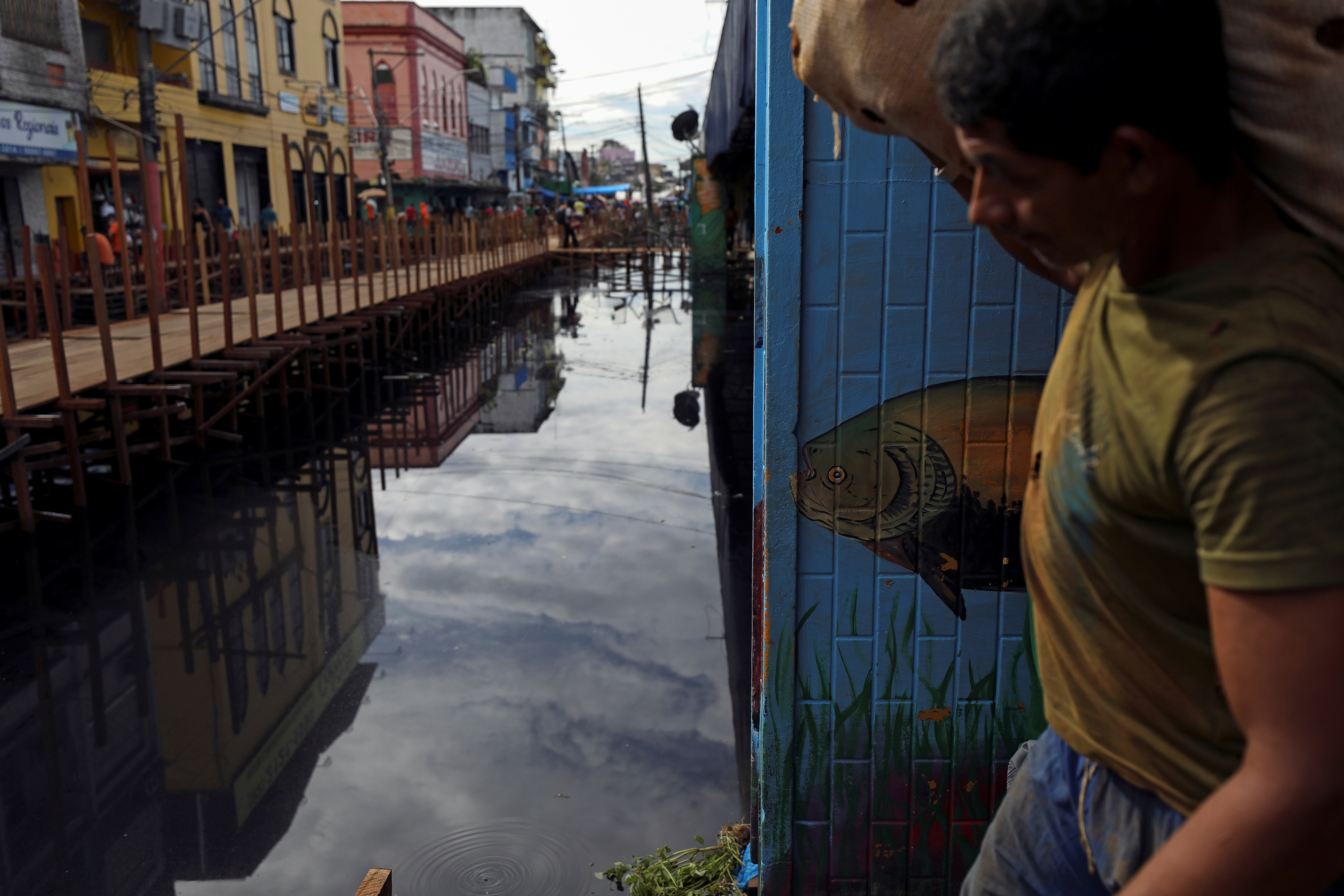 A man carries a bag as he walks over wooden walkways installed by the city hall over a street flooded by waters from the Negro river in downtown of Manaus, in Amazonas State, Brazil May 17, 2021. REUTERS/Bruno Kelly