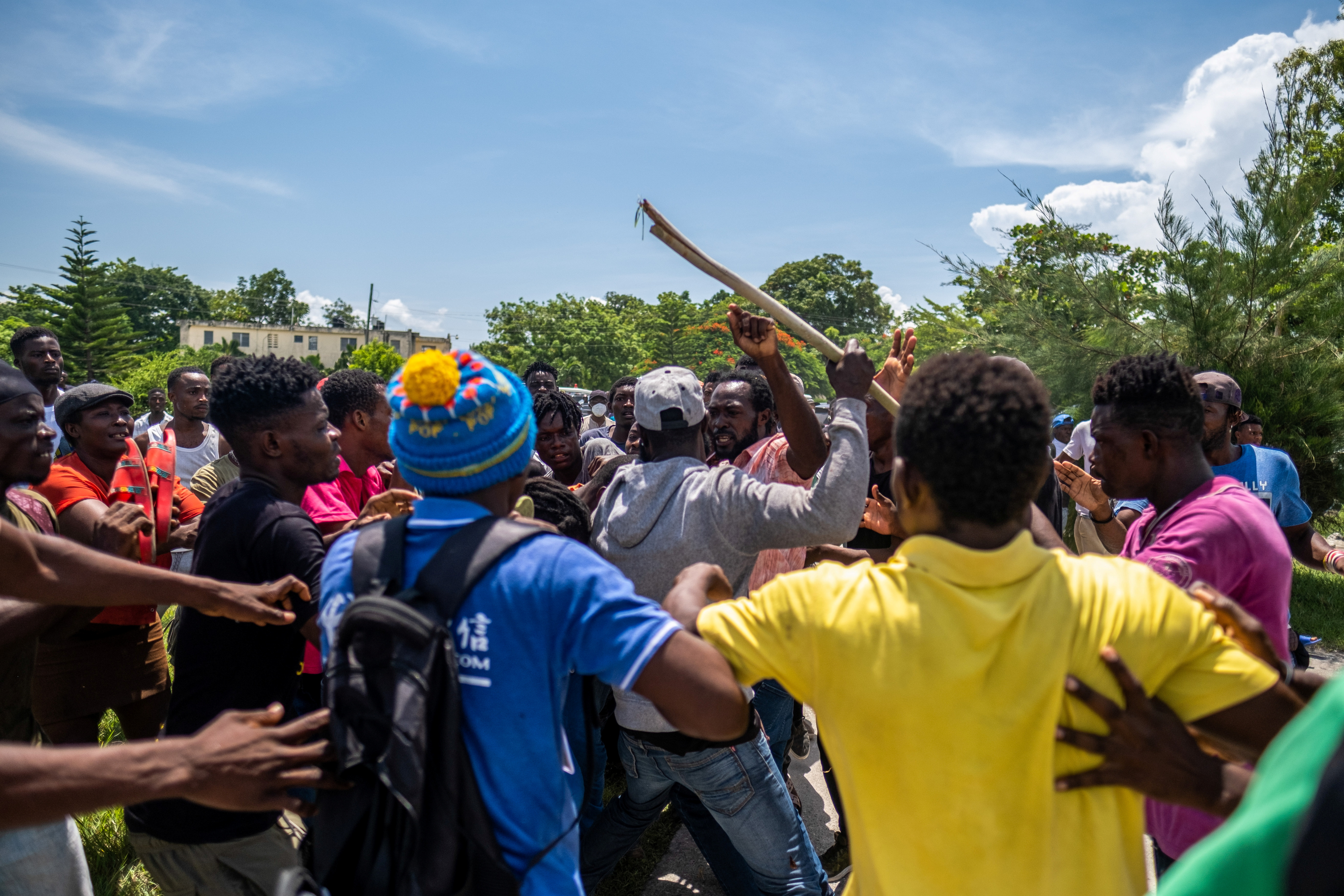 Followers of former Haitian President Michel Martelly fight over an envelope with a cash donation from a Martelly bodyguard during his departure outside the OFATMA hospital after Merely left, in Les Cayes, Haiti August 20, 2021. REUTERS/Ricardo Arduengo
