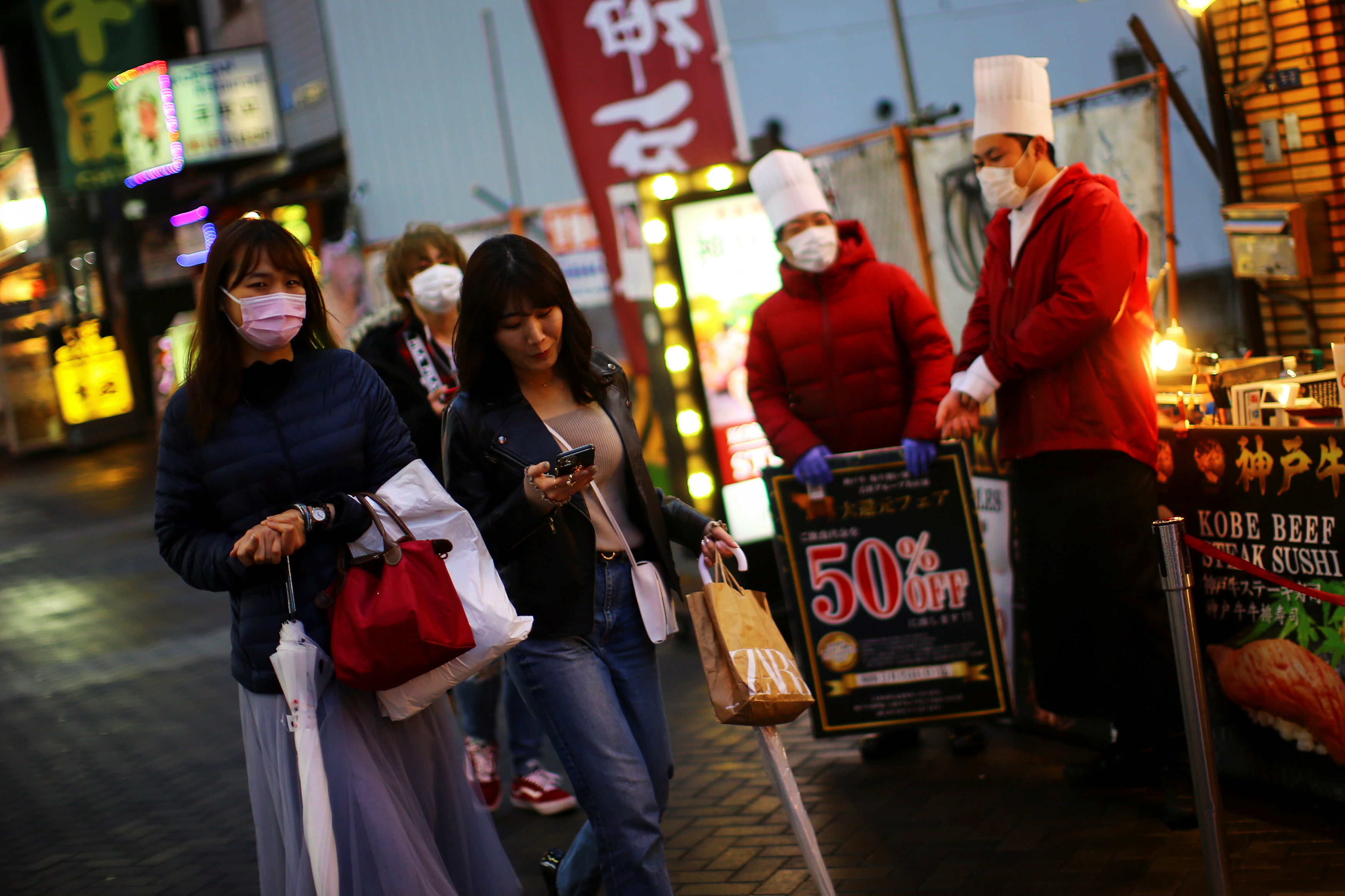 People, wearing protective masks following an outbreak of the coronavirus disease (COVID-19), walk on an almost empty street in the Dotonbori entertainment district of Osaka, Japan, March 14, 2020.   REUTERS/Edgard Garrido