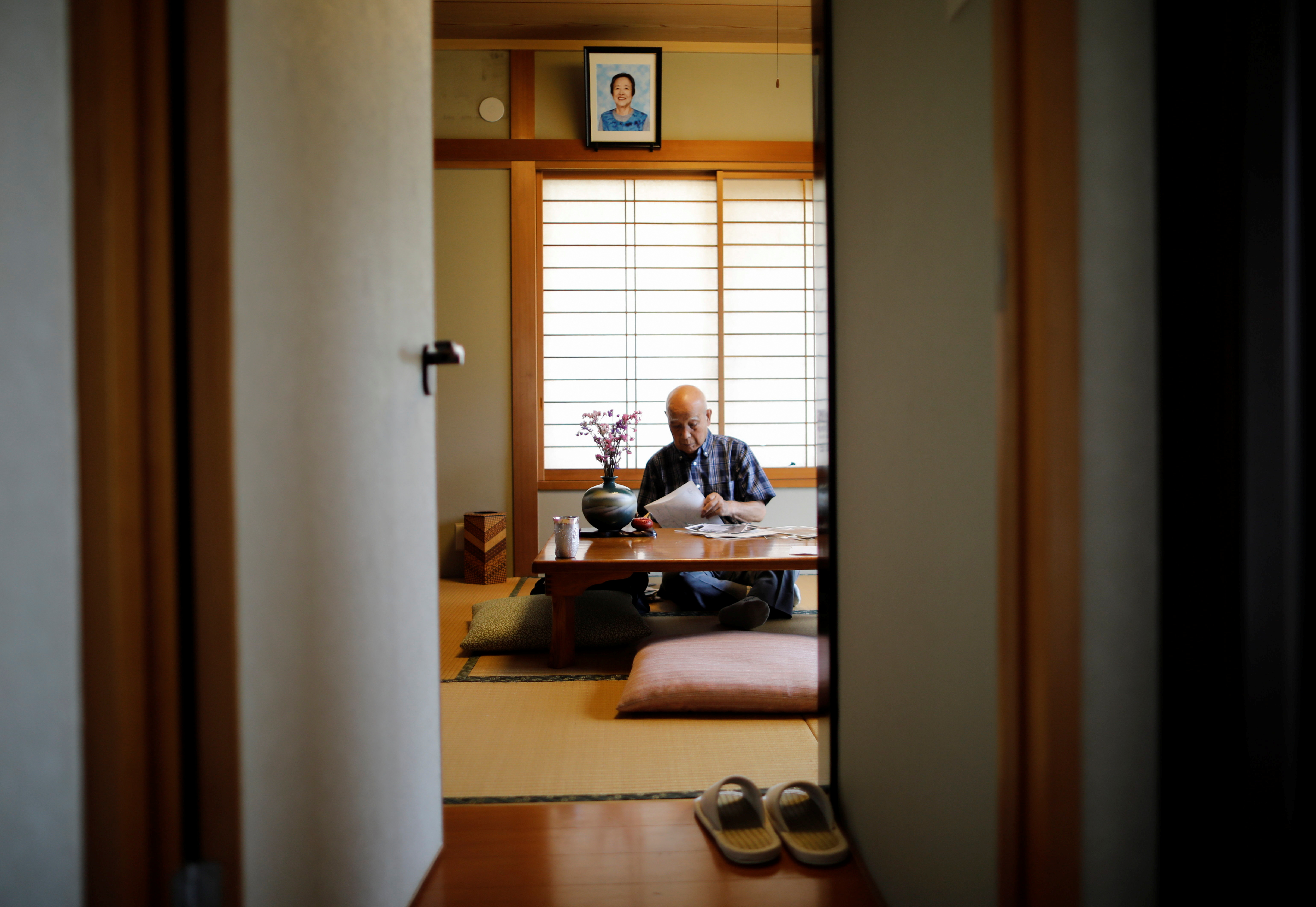 Kohei Jinno, 87, who was forced to leave his house two times ahead of the 1964 and 2020 Olympics Games to make way for construction of the main stadium, pauses under the portrait photo of his late wife Yasuko at his house, in Tokyo, Japan June 24, 2021.  REUTERS/Issei Kato