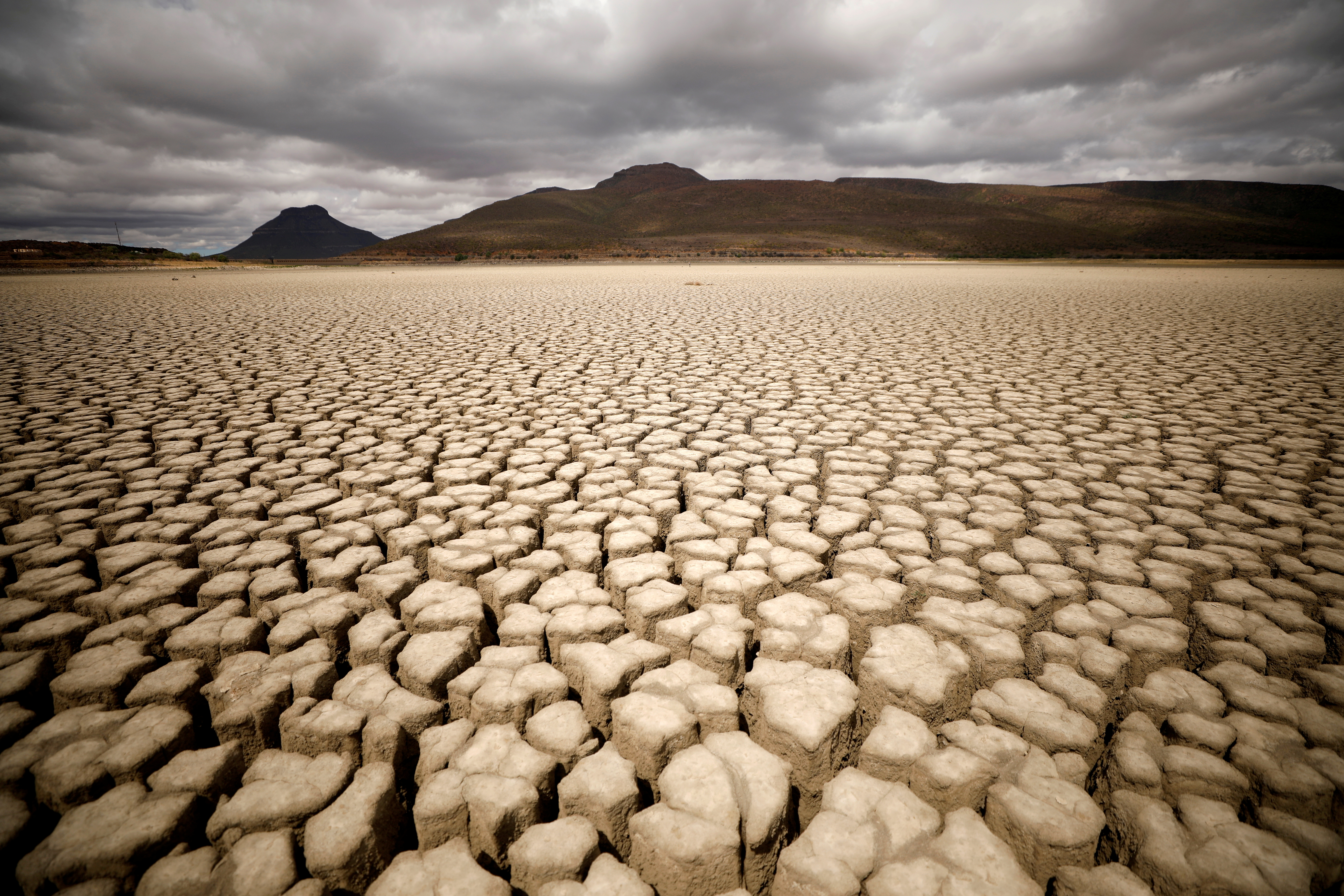 Clouds gather but produce no rain as cracks are seen in the dried up municipal dam in drought-stricken Graaff-Reinet, South Africa, November 14, 2019. REUTERS/Mike Hutchings/File Photo