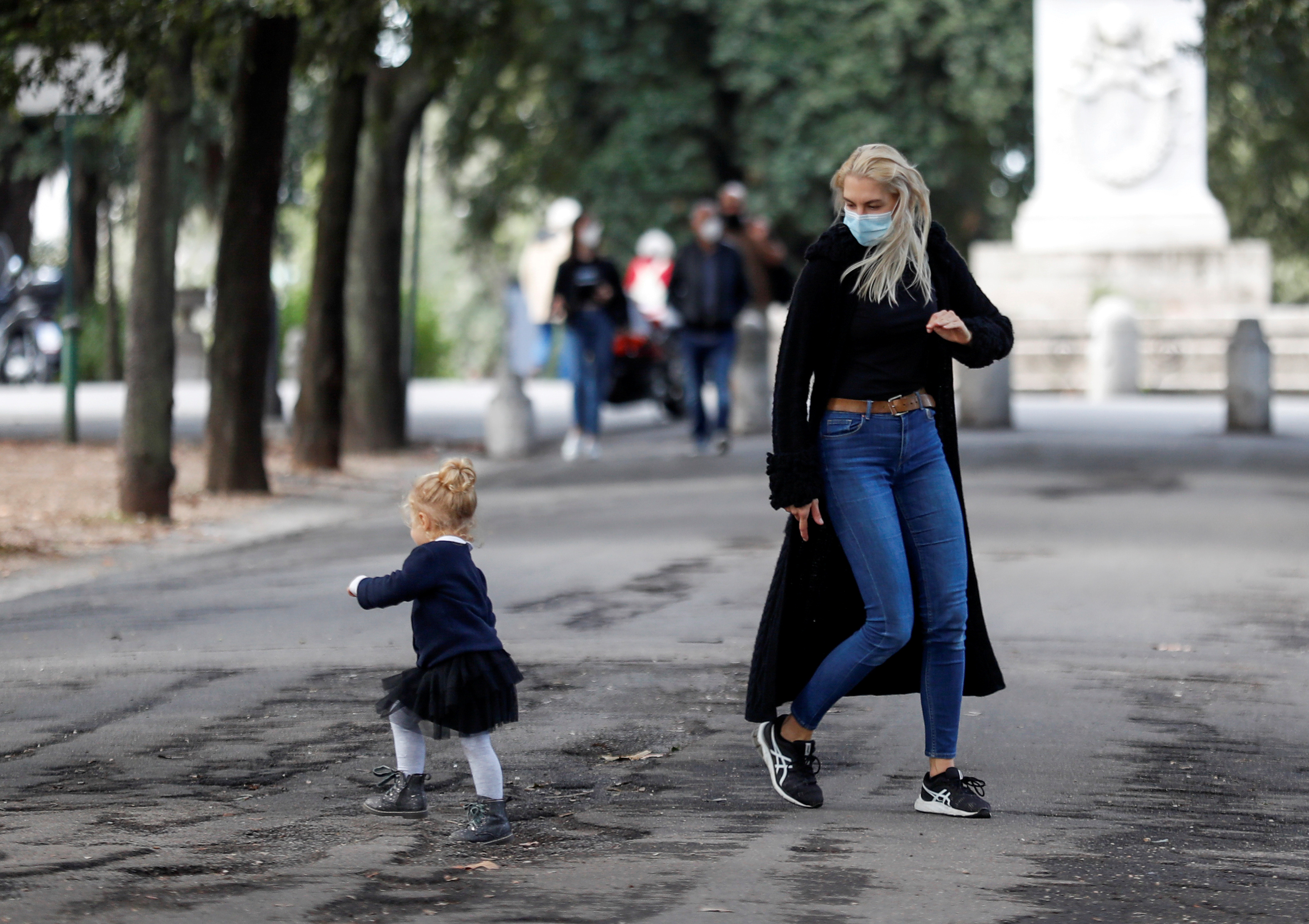 A woman wearing a protective mask plays with a child near Pincio Terrace, amid the outbreak of the coronavirus disease (COVID-19), in Rome, Italy October 13, 2020. REUTERS/Yara Nardi