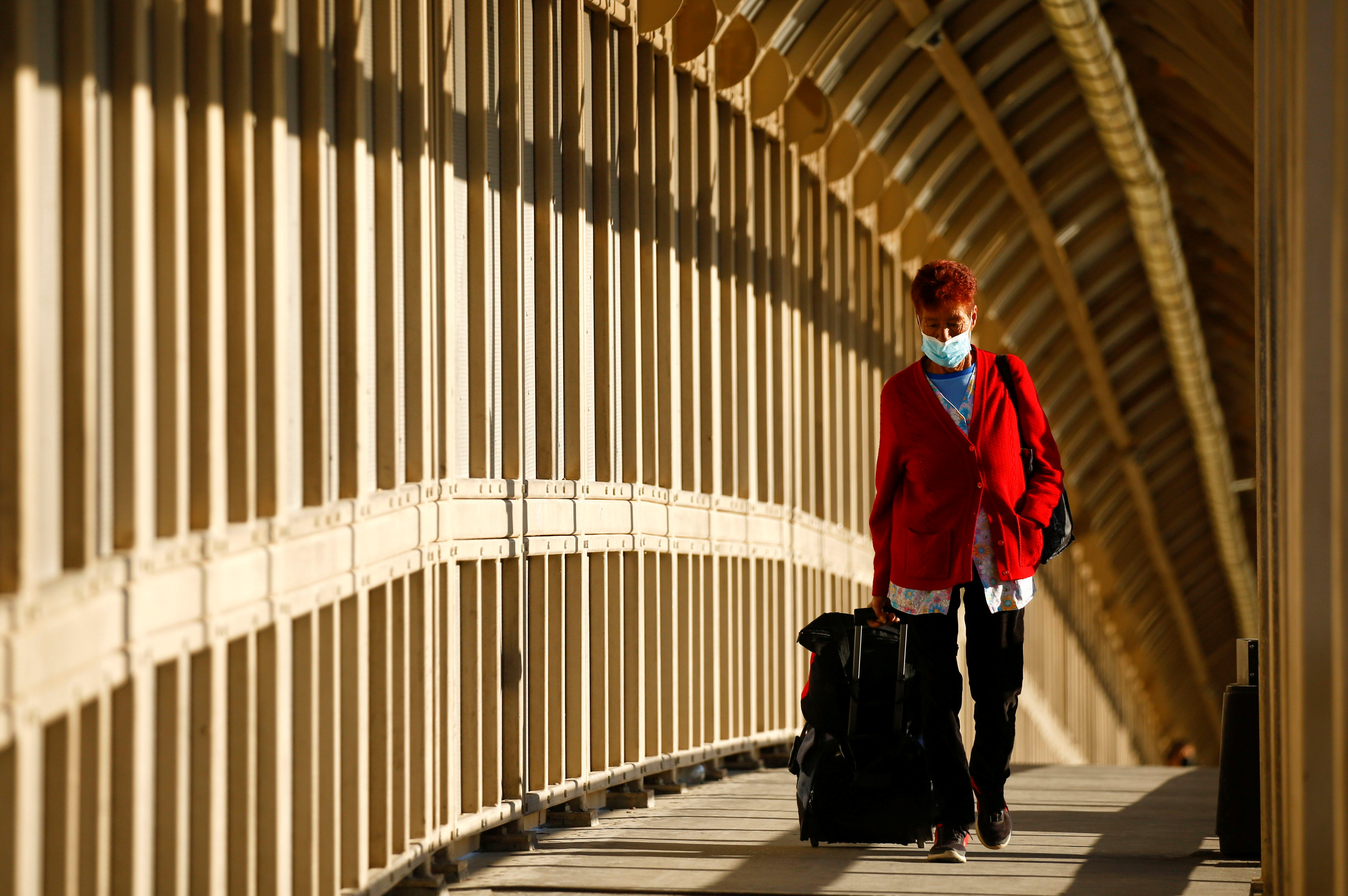 A woman wearing a protective face mask walks towards Mexico at the Paso del Norte International Border bridge after the U.S. Department of Homeland Security extended limits on non-essential travel at land ports of entry, as the coronavirus disease (COVID-19) outbreak continues, in Ciudad Juarez, Mexico May 18, 2021. REUTERS/Jose Luis Gonzalez/File Photo