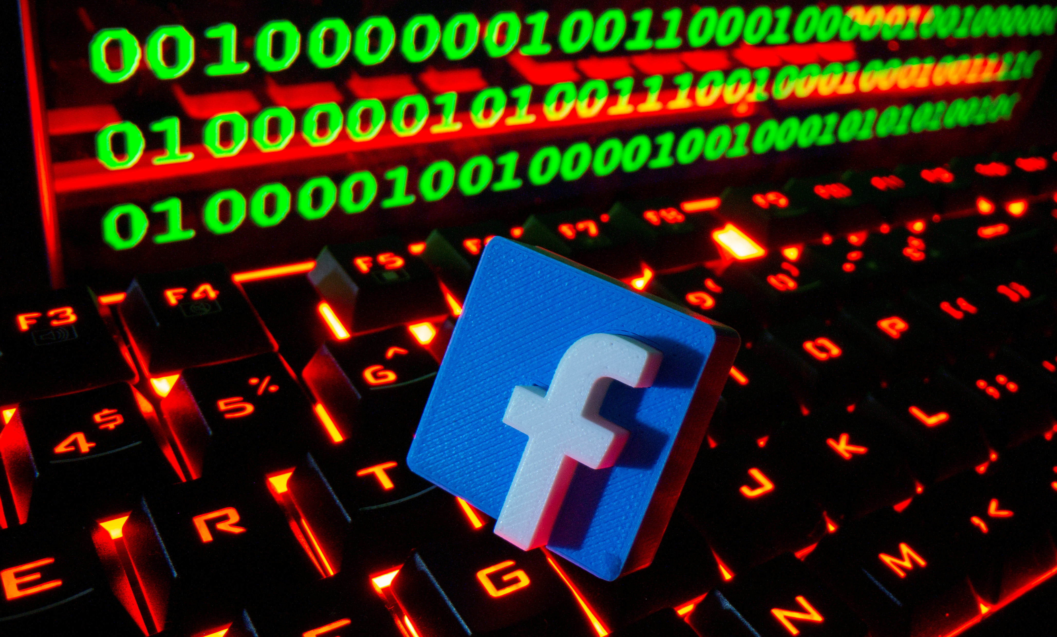 A 3D printed Facebook logo is pictured on a keyboard in front of binary code in this illustration taken September 24, 2021. REUTERS/Dado Ruvic/Illustration