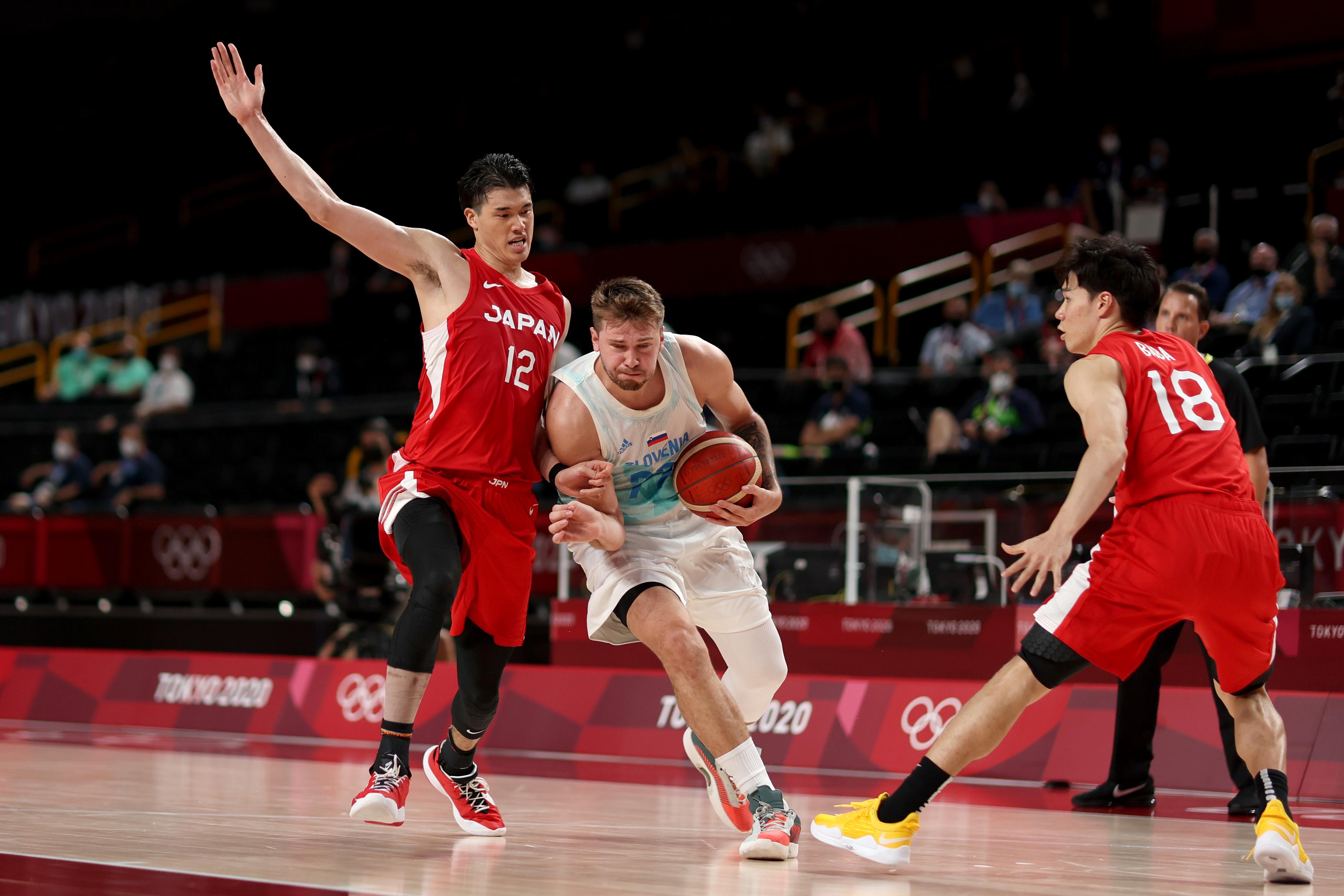 Tokyo 2020 Olympics - Basketball - Men - Group C - Slovenia v Japan - Saitama Super Arena, Saitama, Japan - July 29, 2021. Luka Doncic of Slovenia in action with Y. Watanabe of Japan REUTERS/Alkis Konstantinidis