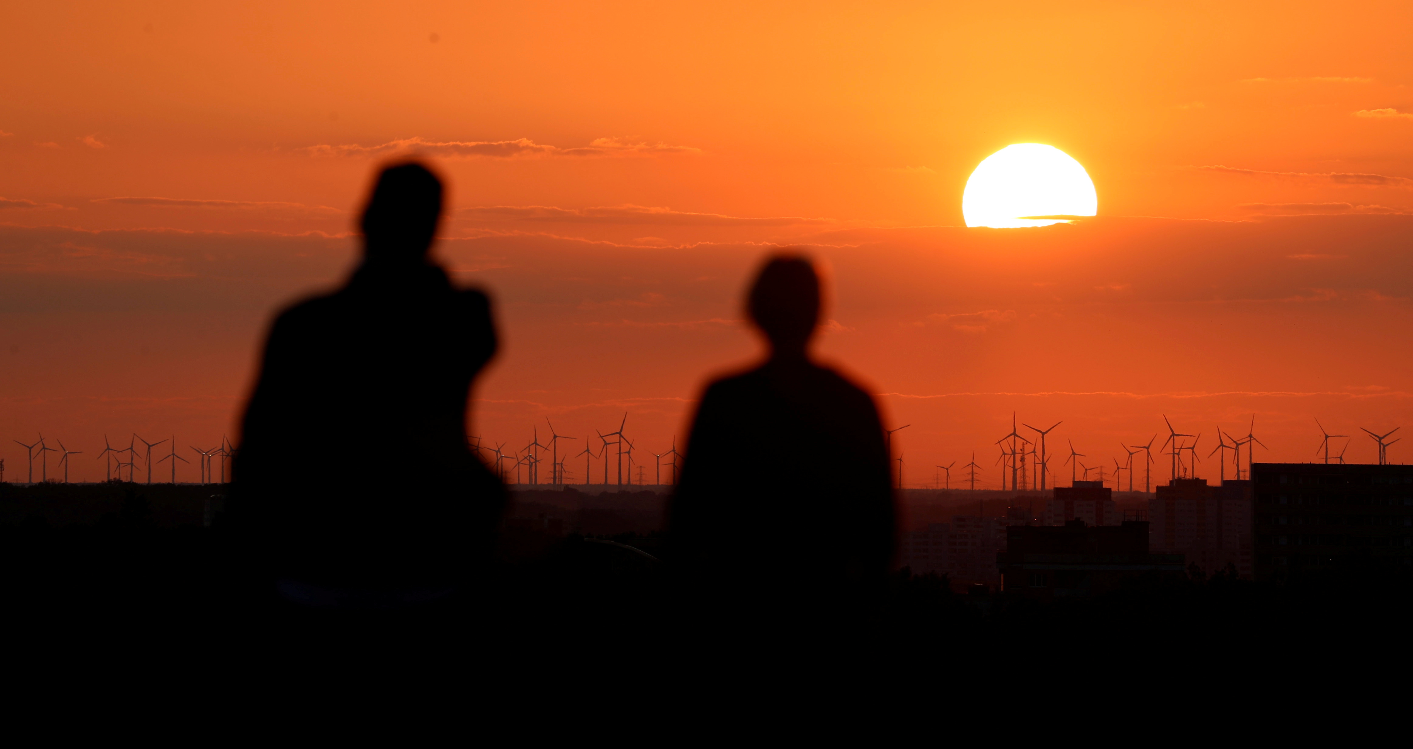 People watch on top of the Drachenberg hill power-generating windmill turbines during sunset in Berlin, Germany, August 19, 2019. REUTERS/Fabrizio Bensch