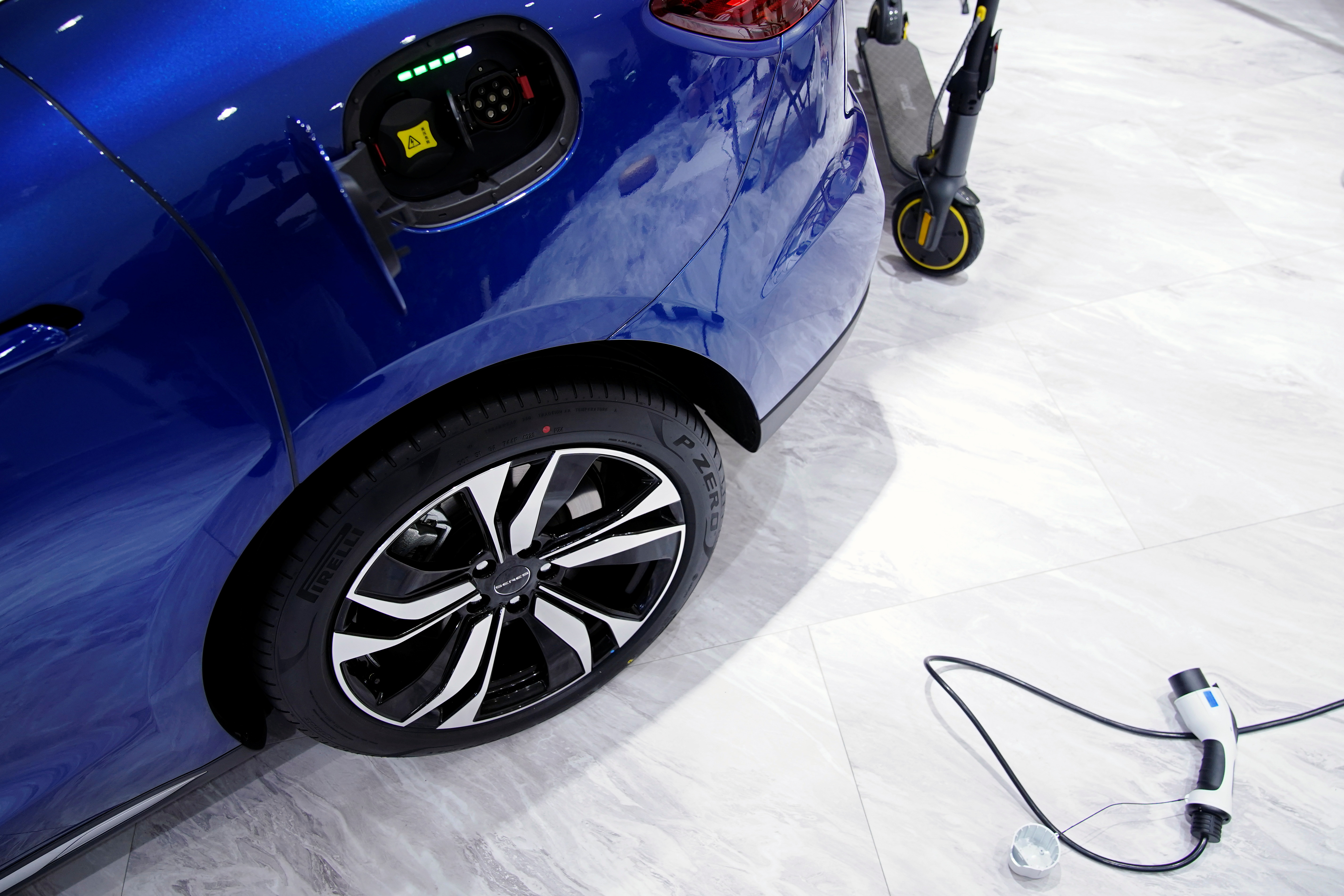 A charging cable is seen next to a Cyrus Huawei Smart Selection SF5 electric vehicle (EV) displayed during a media day for the Auto Shanghai show in Shanghai, China April 20, 2021. REUTERS/Aly Song