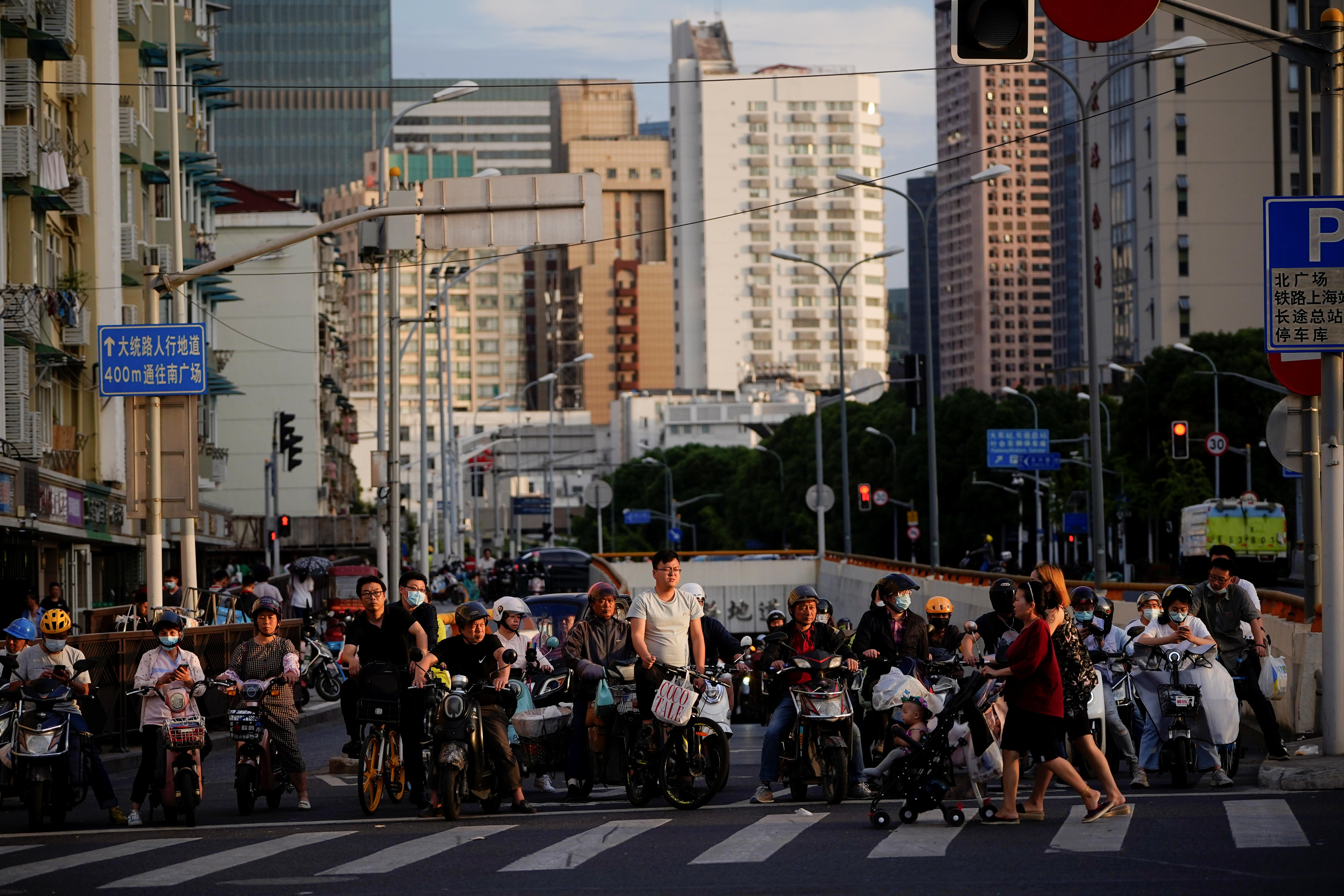 People riding bicycles and motorbikes wait in traffic, amid the coronavirus disease (COVID-19) pandemic, in Shanghai, China May 31, 2021. REUTERS/Aly Song