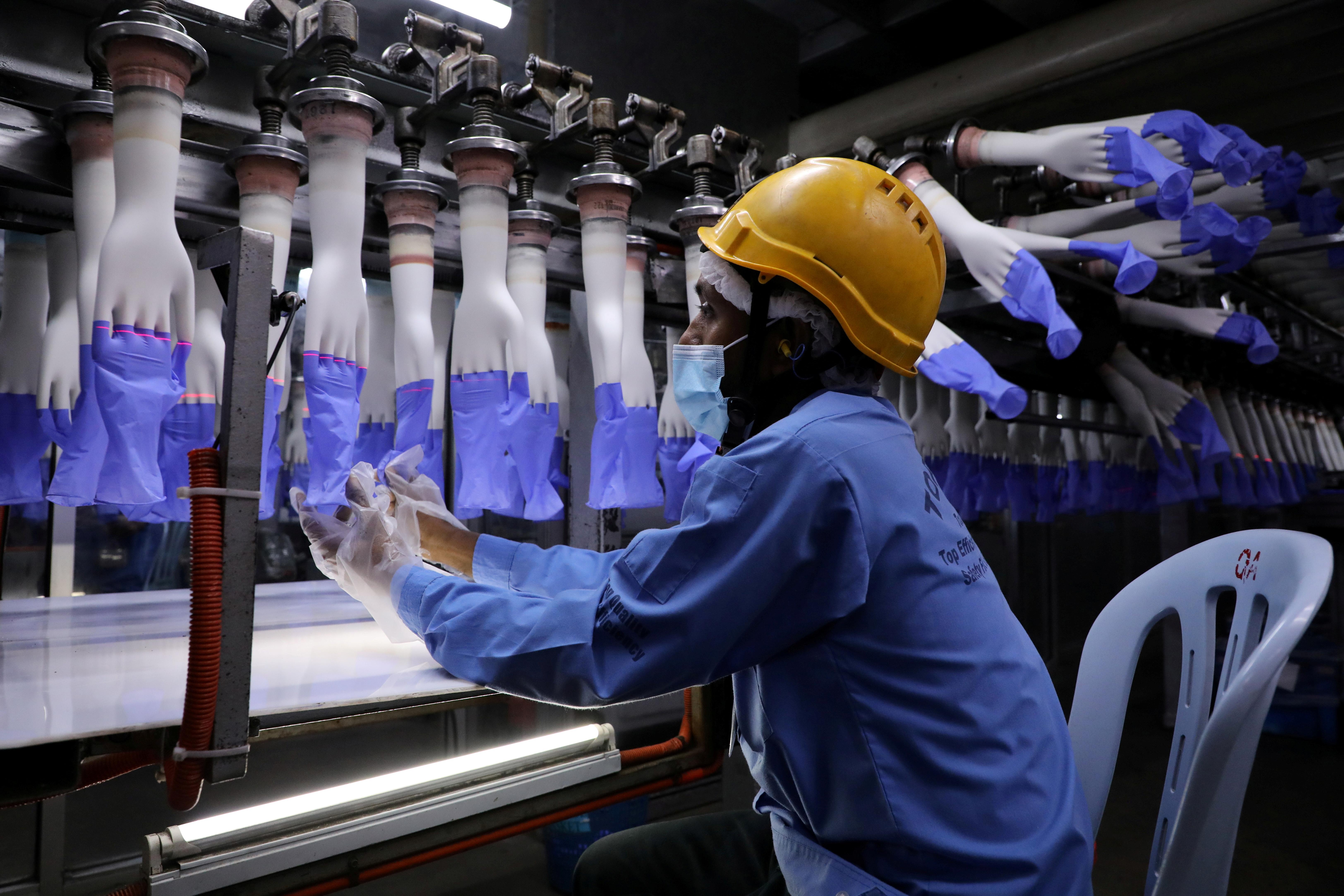 2020년 8월 26일 말레이시아 샤알람의 탑 글로브 공장에서 한 작업자가 새로 만든 장갑을 검사하고 있습니다. REUTERS/Lim Huey Teng/파일 사진