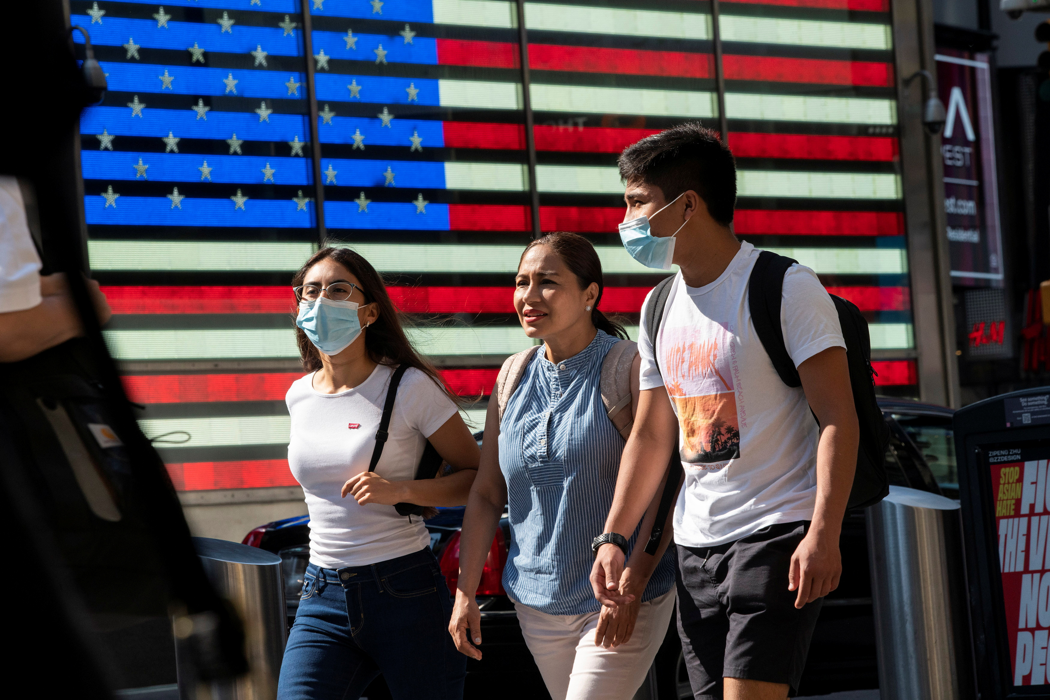 People wear masks around Times Square, as cases of the infectious coronavirus Delta variant continue to rise in New York City, July 23, 2021. REUTERS/Eduardo Munoz