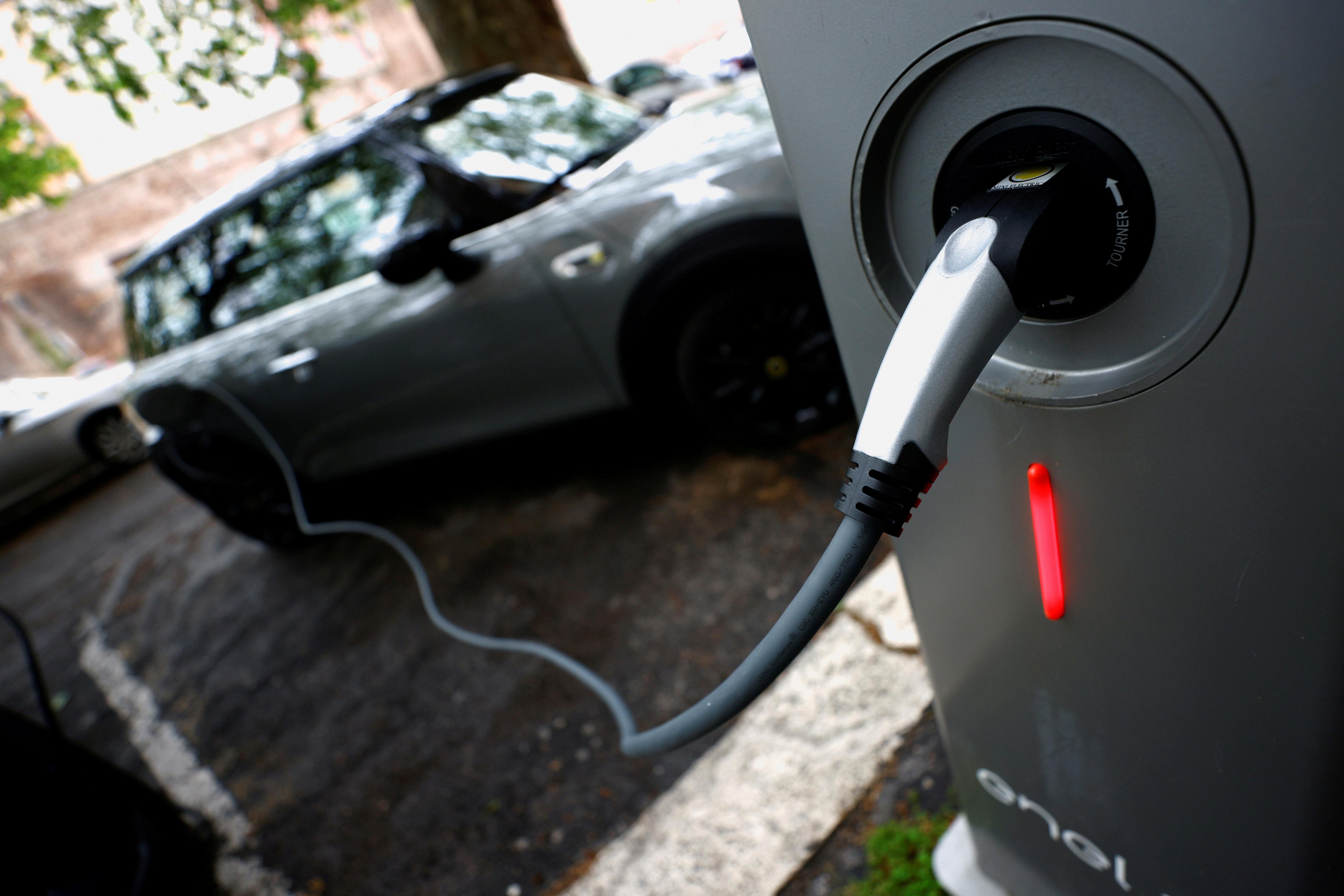 En elektrisk bil sees plugget inn ved et ladepunkt for elektriske kjøretøyer i Roma, Italia, 28. april 2021. REUTERS / Guglielmo Mangiapane