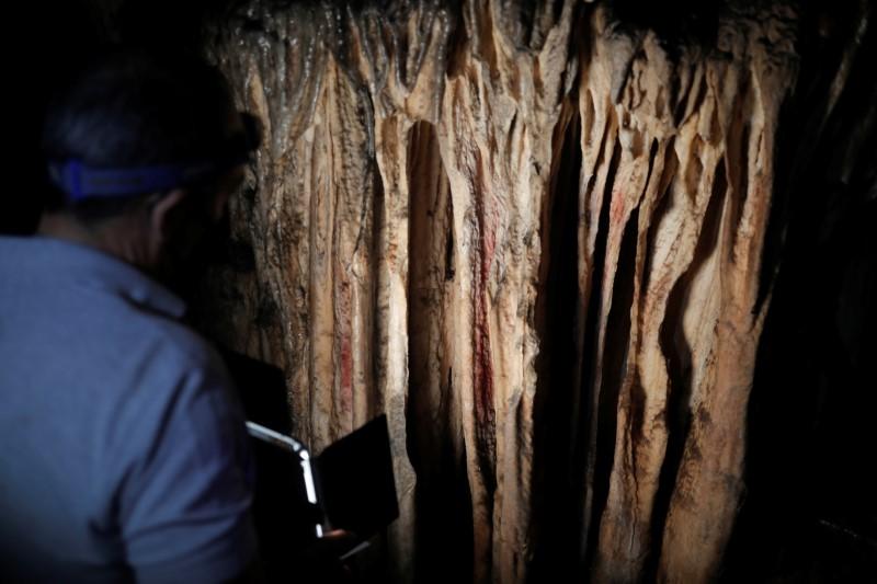 Mae canllaw yn goleuo marciau ocr coch a baentiwyd ar stalagmites gan Neanderthaliaid tua 65,000 o flynyddoedd yn ôl, yn ôl astudiaeth ryngwladol, mewn ogof gynhanesyddol yn Ardales, de Sbaen, Awst 7, 2021. REUTERS / Jon Nazca