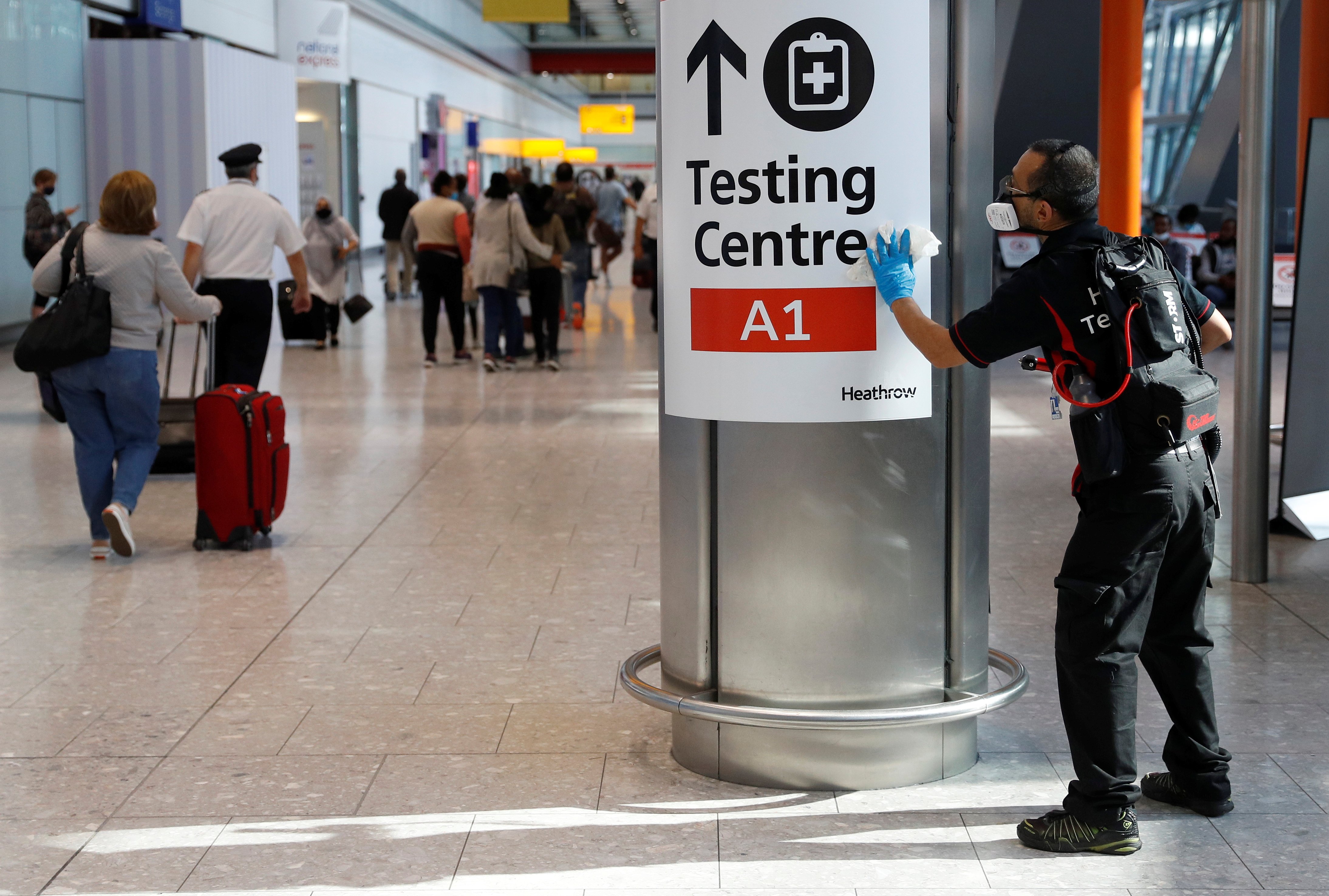 A worker sanitises a sign at the International arrivals area of Terminal 5 in London's  Heathrow Airport, Britain, August 2, 2021.  REUTERS/Peter Nicholls
