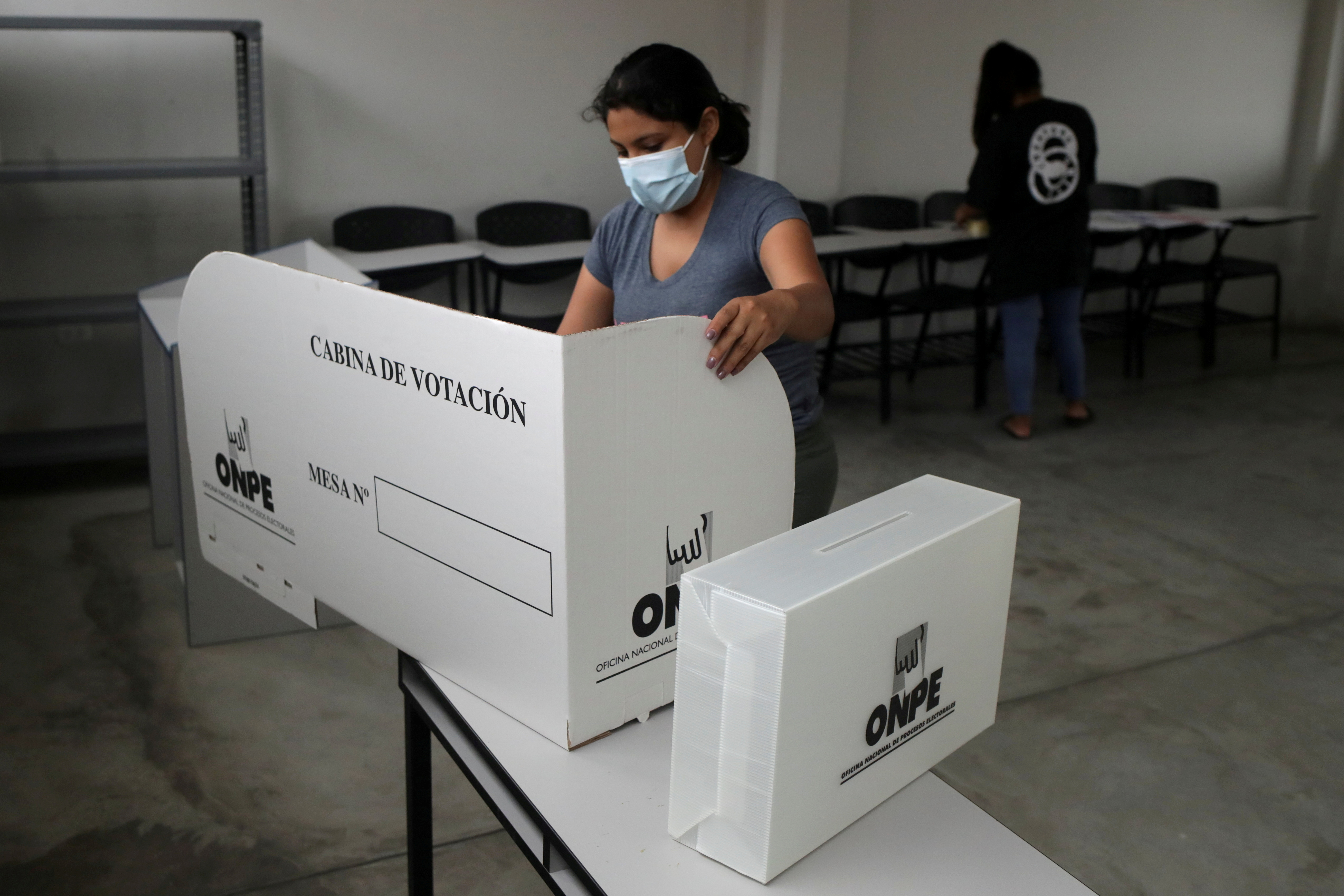 A member of electoral personnel sets up a voting booth, the day ahead of the first round of presidential and parliamentary elections, at a polling station in San Juan Miraflores neighborhood in Lima, Peru, April 10, 2021. REUTERS/Henry Romero/File Photo