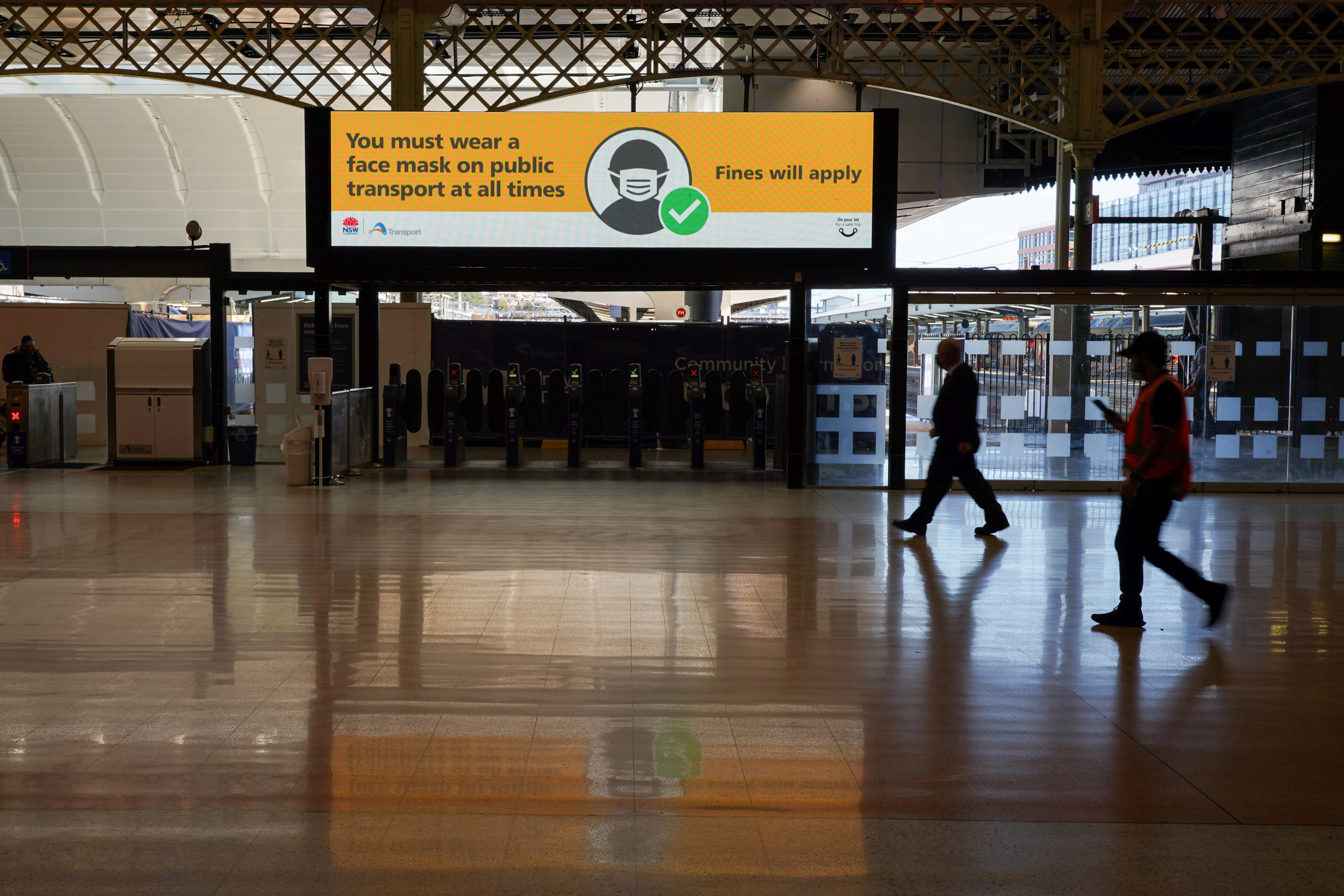 People walk past a public health message regarding the wearing of masks on public transport, at the quiet Central Station during a COVID-19 lockdown in Sydney, Australia, August 20, 2021.  REUTERS/Loren Elliott