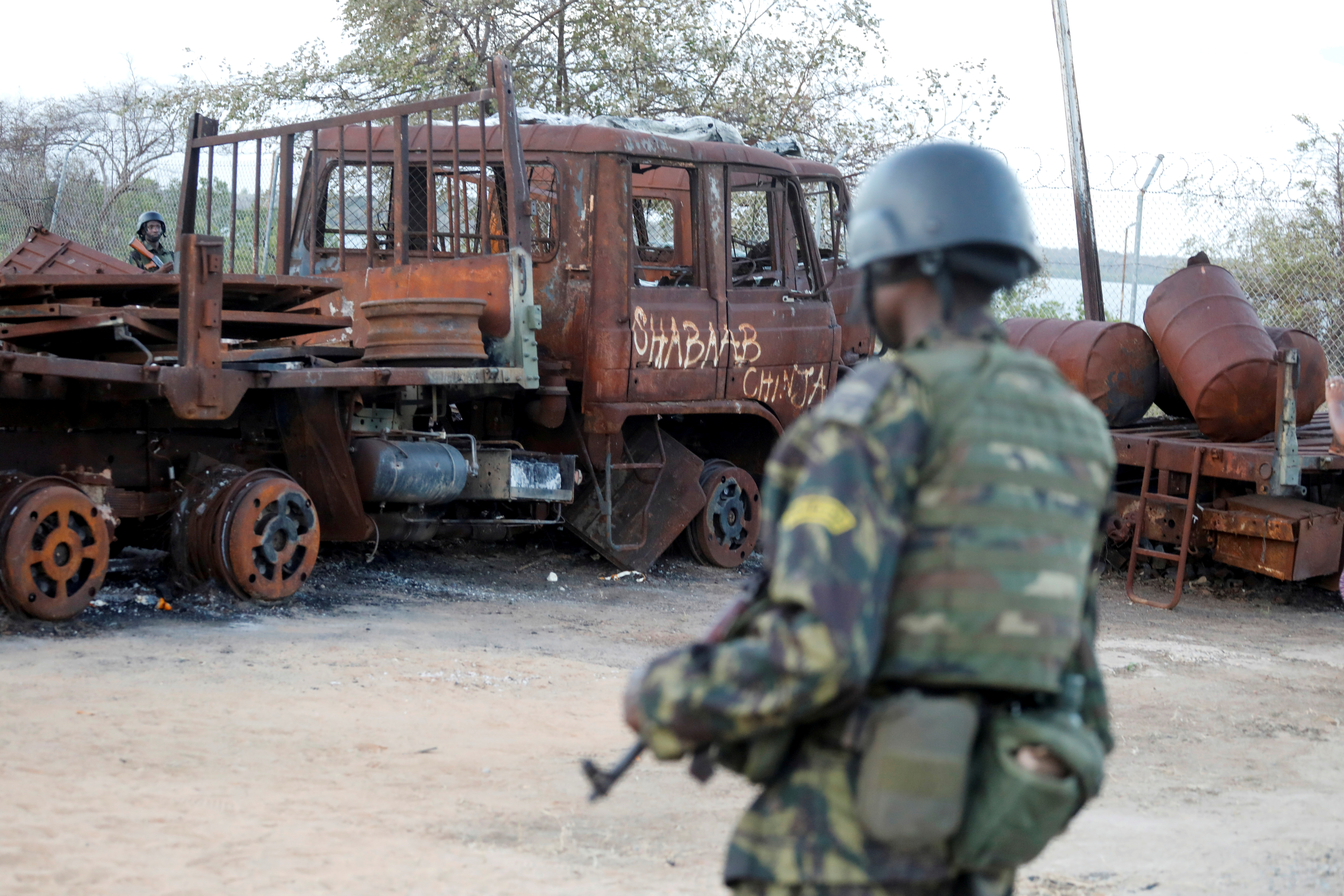 A Rwandan security forces soldier walks past a burned truck at the port of Mocimboa da Praia, Mozambique September 22, 2021. The graffiti reads