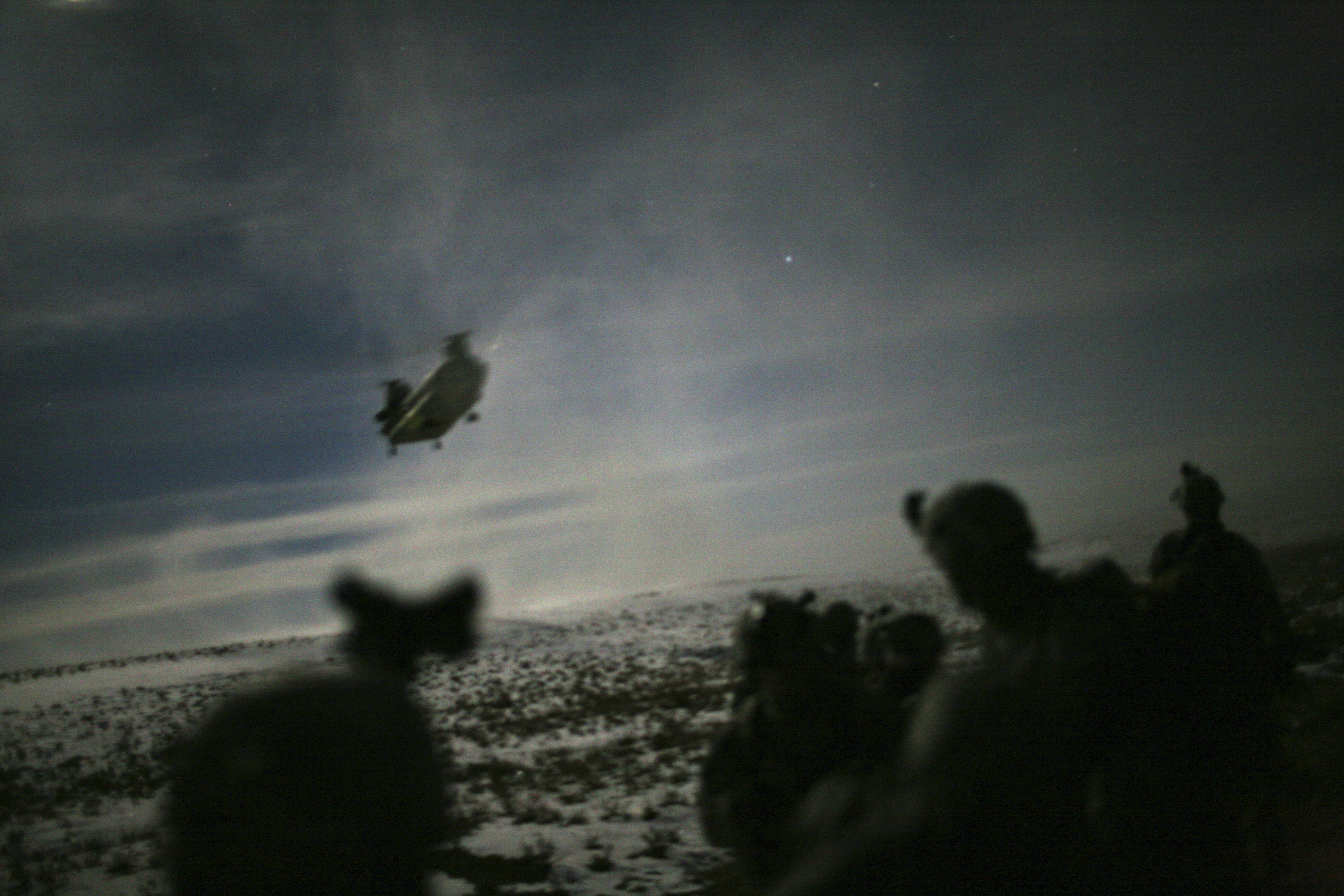 A Chinook helicopter lands to pick up U.S. soldiers of the 101st Airborne Division following a night raid in Yahya Khel, Paktika province February 21, 2011. The night raid is a controversial tactic that has been stepped up dramatically since General David Petraeus took over running the Afghan war last year, despite strong opposition led by President Hamid Karzai. Petraeus says the pressure on suspected insurgents and their networks has brought a new dynamic to a near-decade-old war. Critics argue it is fuelling violence because poor intelligence means dozens of innocent people are killed or detained. Although more than 80 percent of recent raids ended without a shot being fired, violence escalates fast when it does break out, with 600 people killed on operations in the three-month period.    To match Feature AFGHANISTAN-RAIDS/   Picture taken February 21, 2011. REUTERS/Matt Robinson (AFGHANISTAN - Tags: CIVIL UNREST MILITARY POLITICS IMAGES OF THE DAY) - GM1E72O17Q701