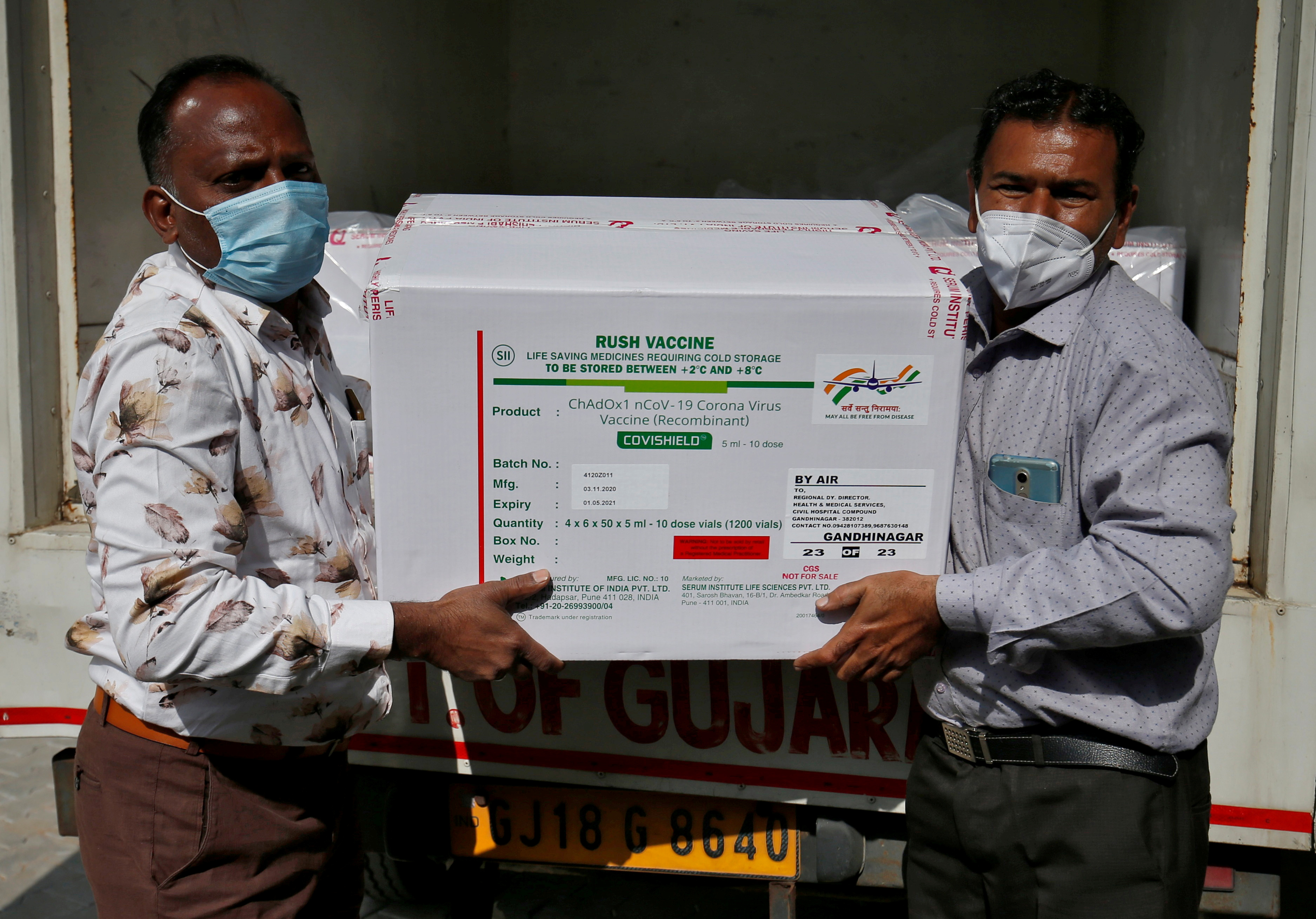 Officials unload boxes containing vials of AstraZeneca's COVISHIELD, a coronavirus disease (COVID-19) vaccine manufactured by Serum Institute of India,  outside a vaccination storage centre in Ahmedabad, India, January 12, 2021. REUTERS/Amit Dave