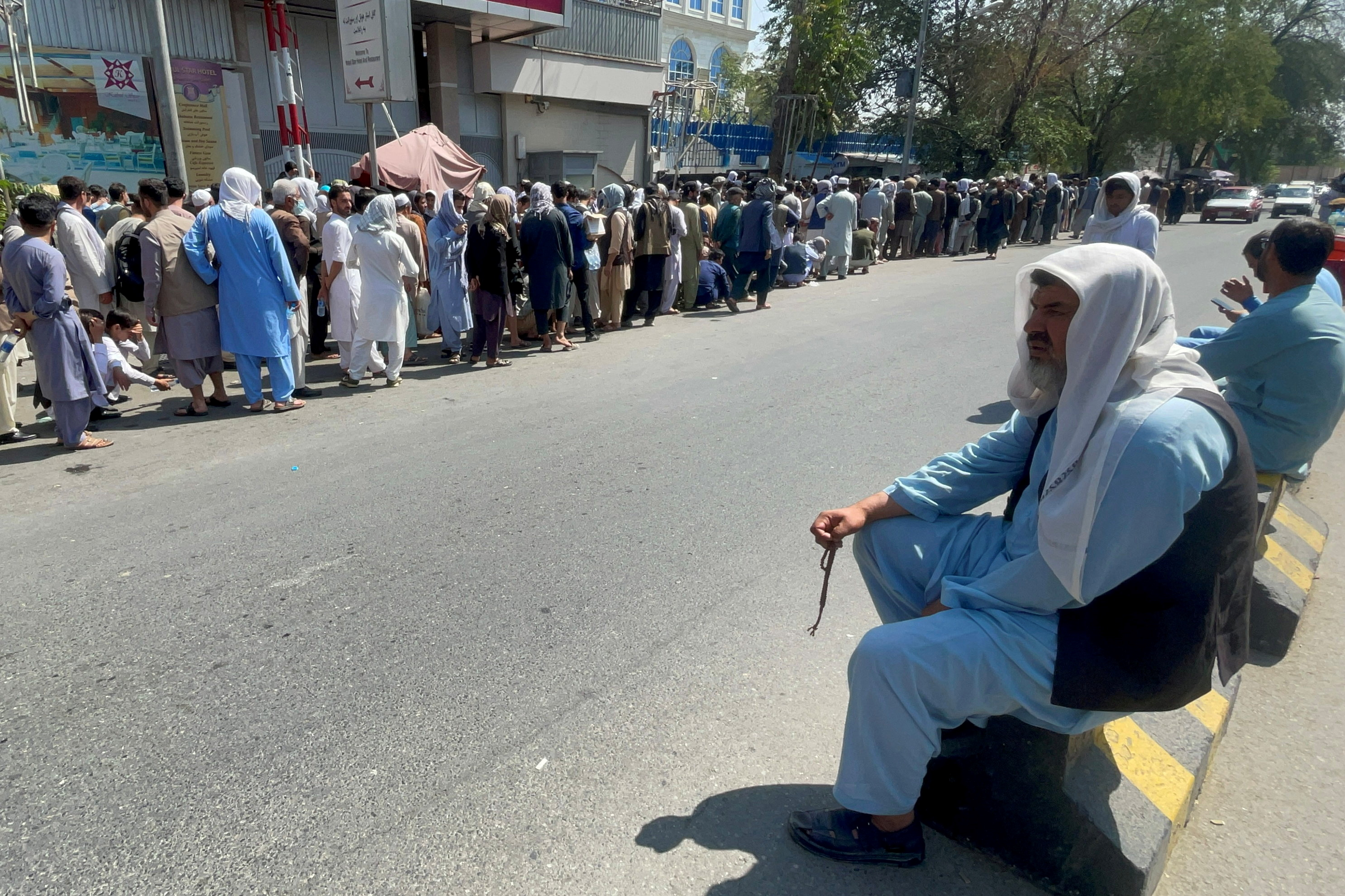Afghans line up outside a bank to take out their money after Taliban takeover in Kabul, Afghanistan September 1, 2021. REUTERS/Stringer/File Photo