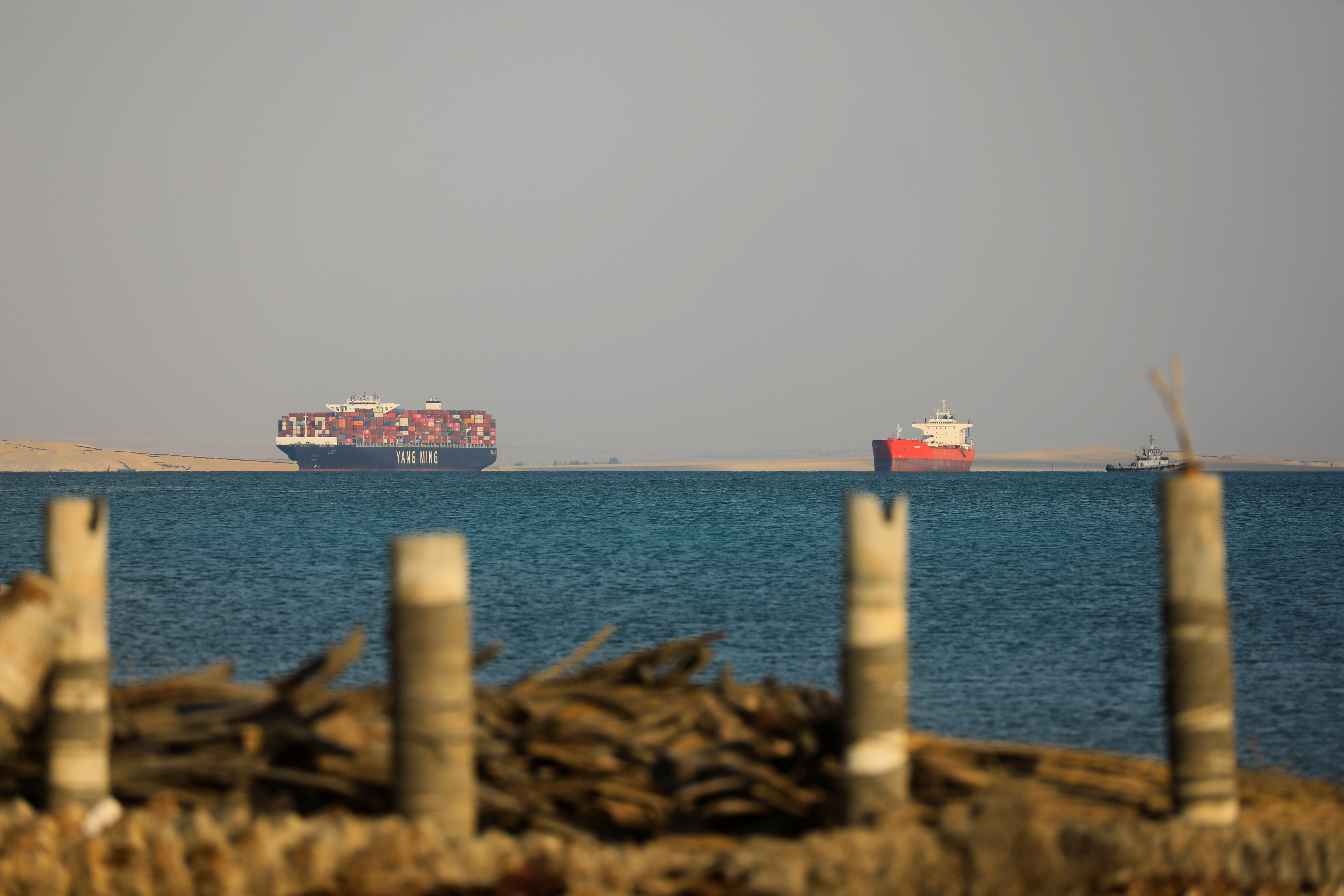 A Yang Ming cargo ship and another ship are anchored outside the Suez Canal, where a container ship ran aground and blocked traffic, in Ismailia, Egypt March 25, 2021. REUTERS/Amr Abdallah