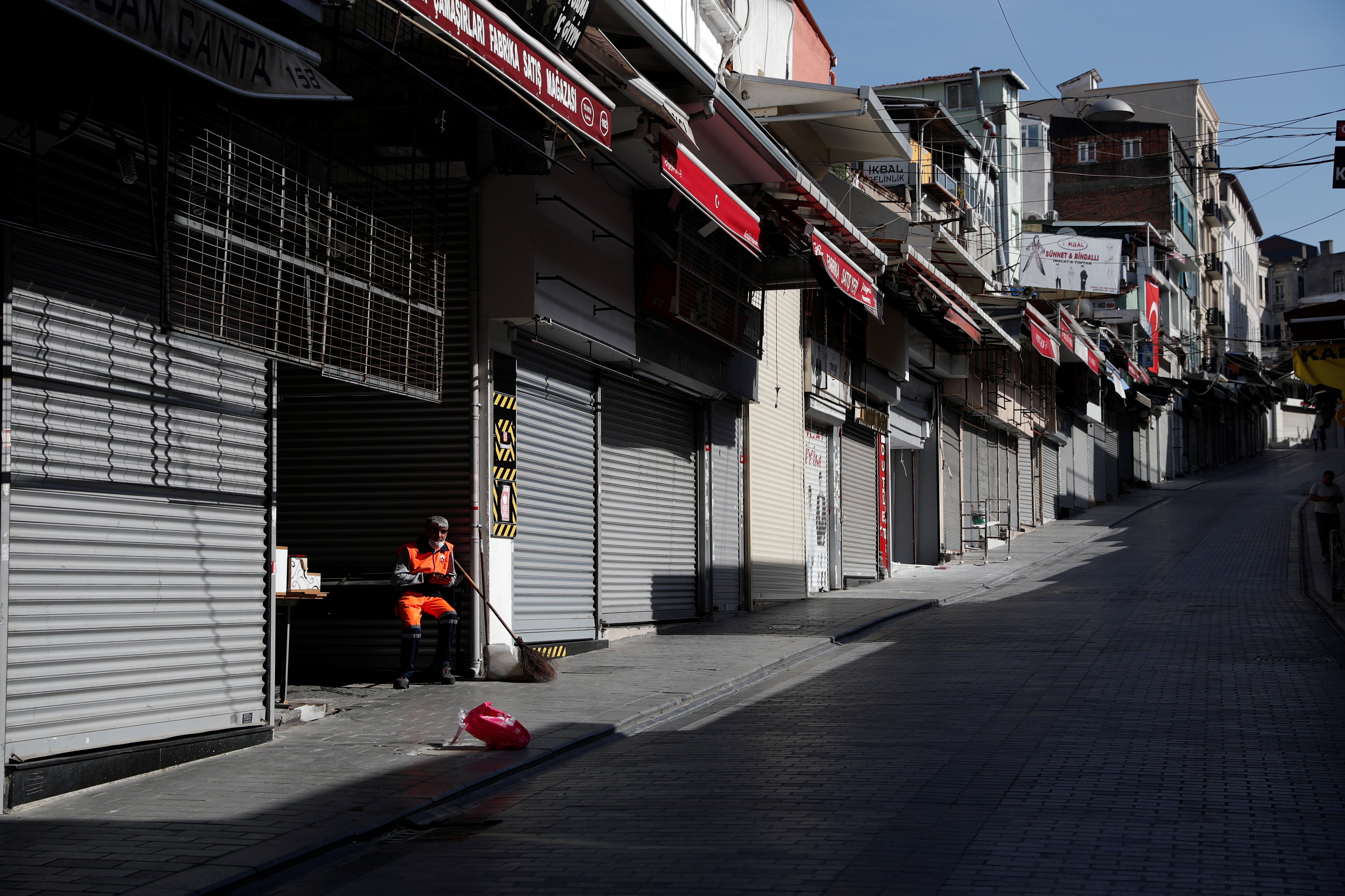A street cleaner pauses at deserted Mahmutpasa street, a popular middle-class shopping district, during a nationwide