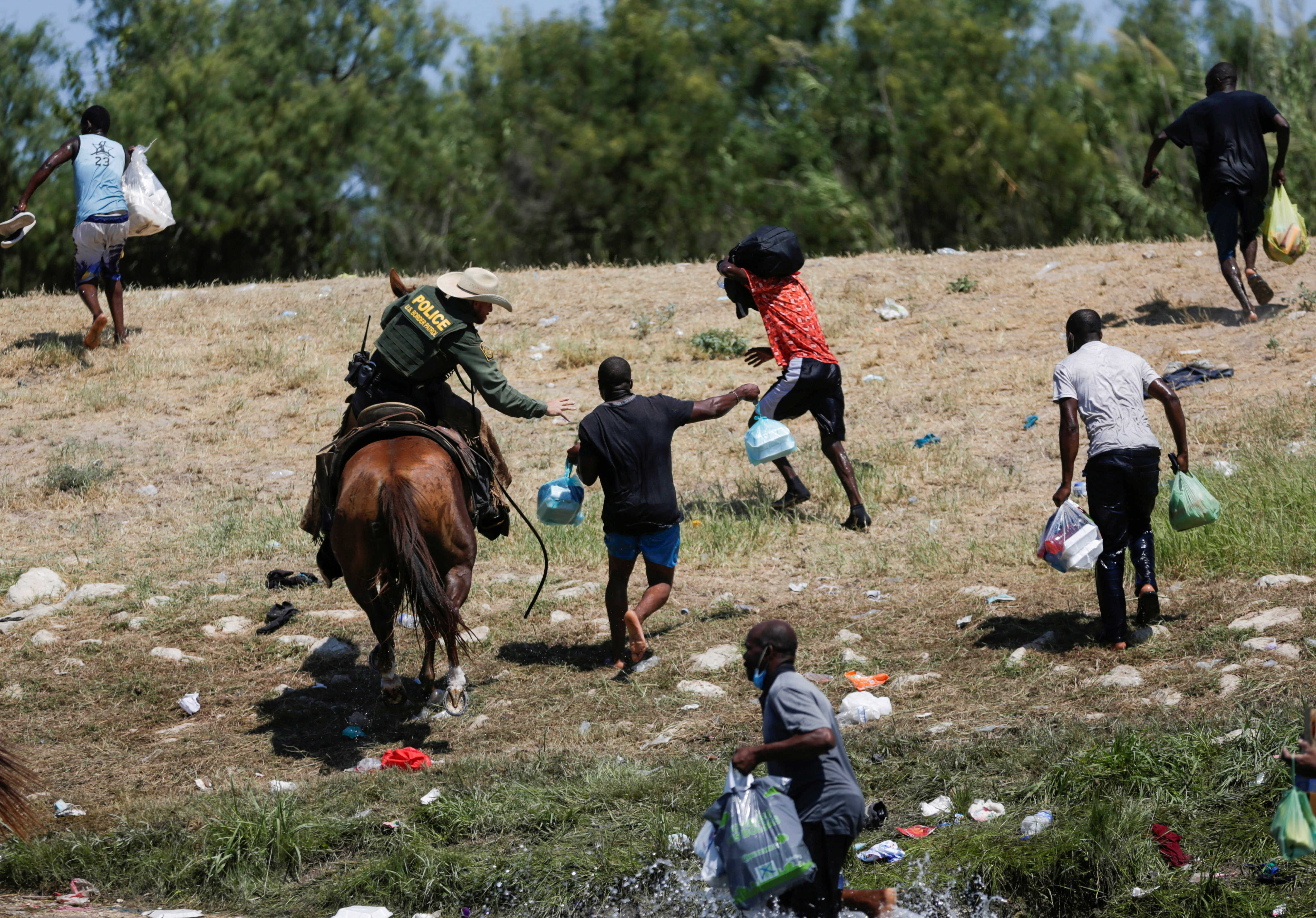 A U.S. law enforcement officer on horseback chases migrants returning to the United States after buying food in Mexico, as seen from Ciudad Acuna, Mexico September 19, 2021. Picture taken September 19, 2021. REUTERS/Daniel Becerril