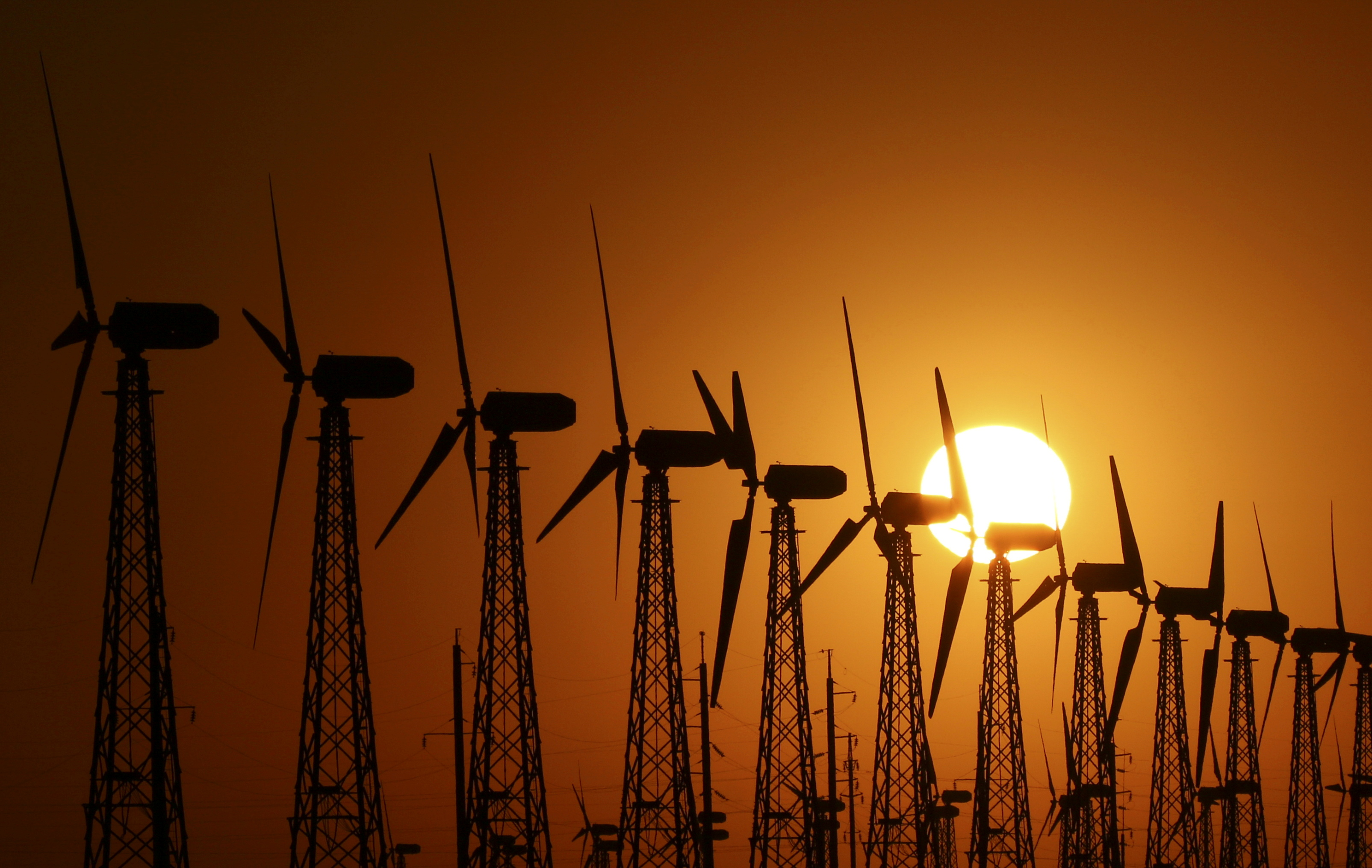 The sun sets behind power-generating turbines of a local wind farm in the settlement of Mirnyi, Crimea June 1, 2018. REUTERS/Pavel Rebrov