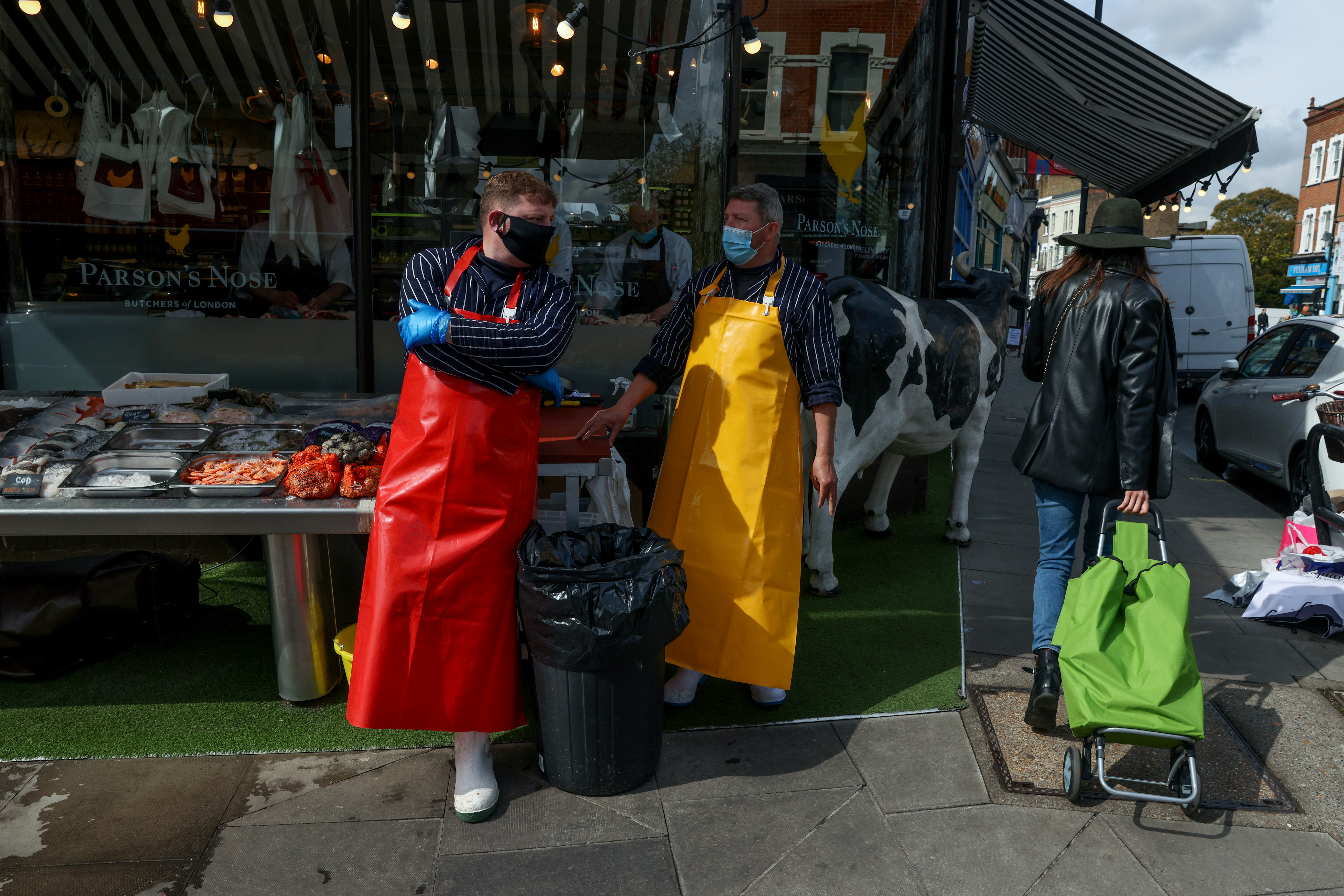 Fishmongers John Arkle and Paul Greenslade work at a fish stall outside a butcher's shop on the Fulham Road, in Fulham, London, Britain May 6, 2021. REUTERS/Kevin Coombs