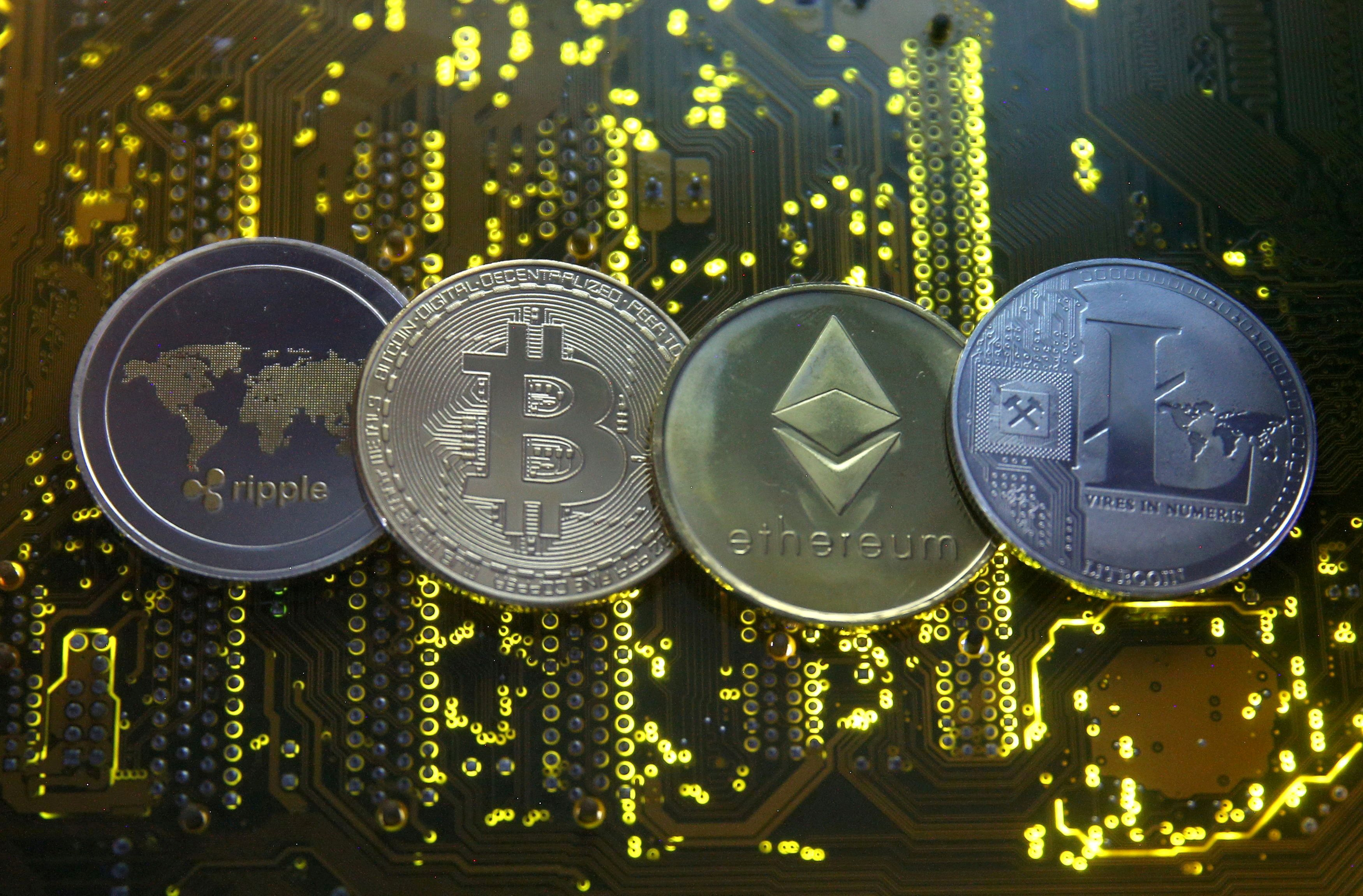 Representations of the Ripple, bitcoin, etherum and Litecoin virtual currencies are seen on a PC motherboard in this illustration picture, February 14, 2018. REUTERS/Dado Ruvic/Illustration