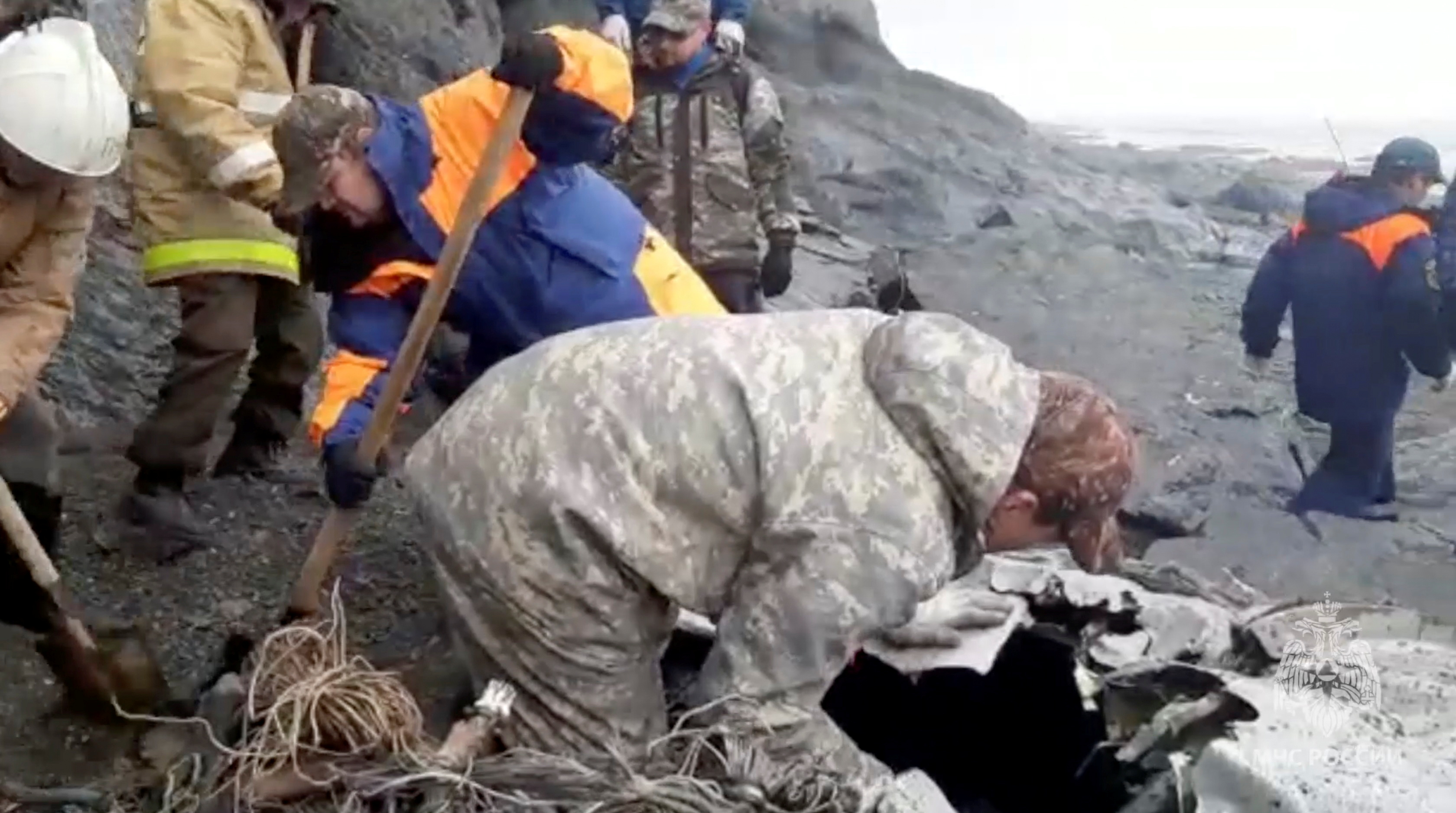 Specialists of the Russian Emergencies Ministry are seen at the crash site of a Russian An-26 passenger plane near the village of Palana in the north of the Kamchatka peninsula, Russia, in this still image taken from video, July 7, 2021.  Russia's Emergencies Ministry/Handout via REUTERS