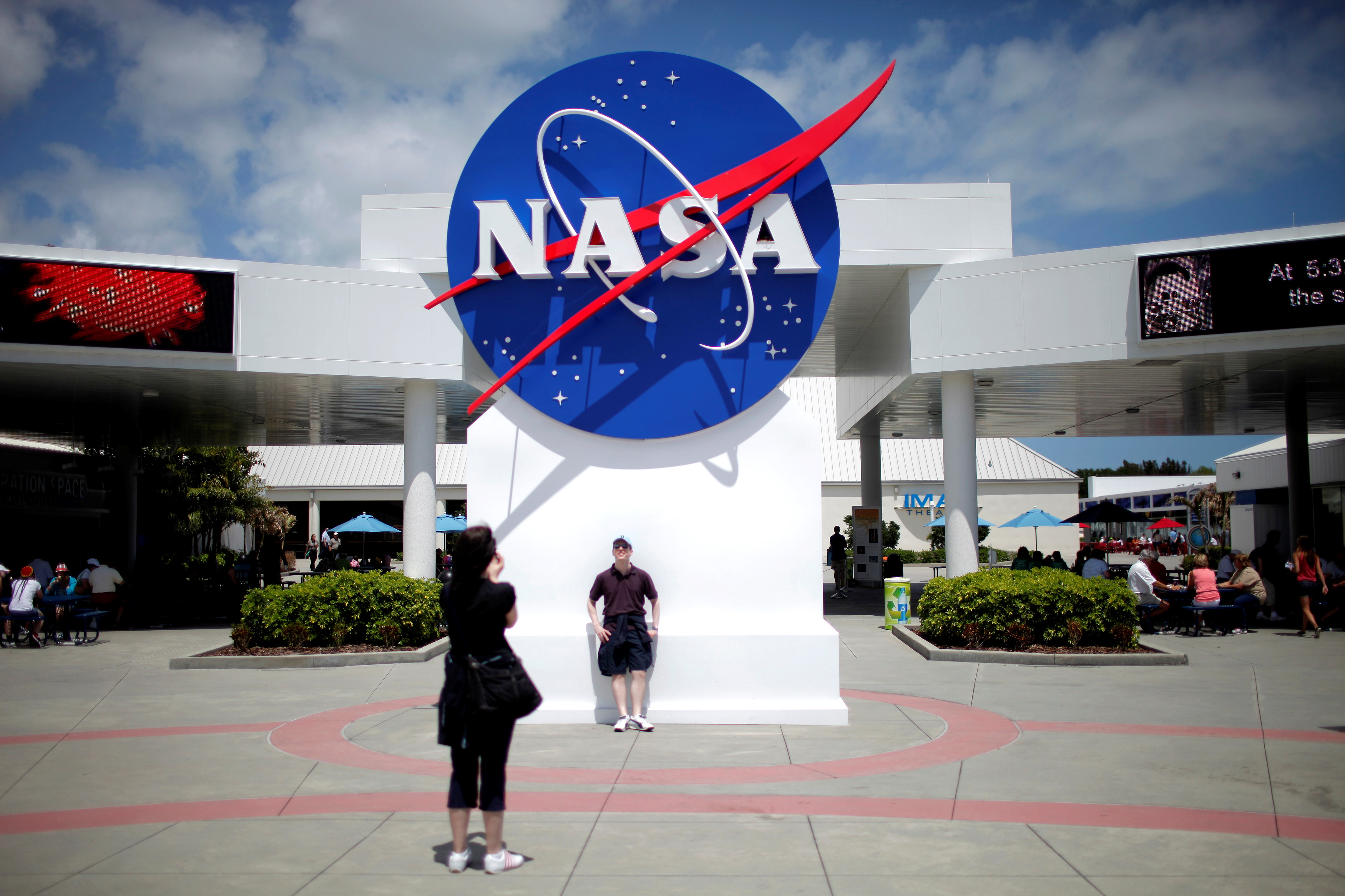 Tourists take pictures of a NASA sign at the Kennedy Space Center visitors complex in Cape Canaveral, Florida April 14, 2010.  REUTERS/Carlos Barria/File Photo