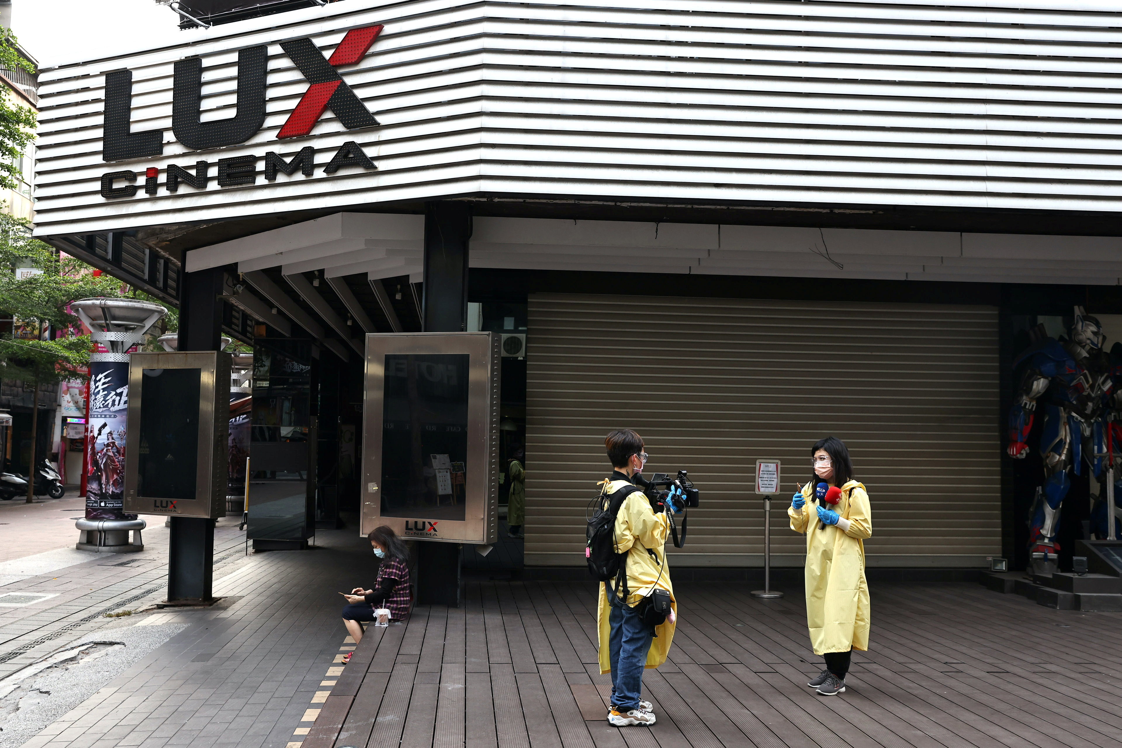 Reporters in protective gear work in front of a closed cinema, after the cinemas and other venues were ordered to close amid an increasing number of COVID-19 infections, in Taipei, Taiwan, May 15, 2021. REUTERS/Ann Wang
