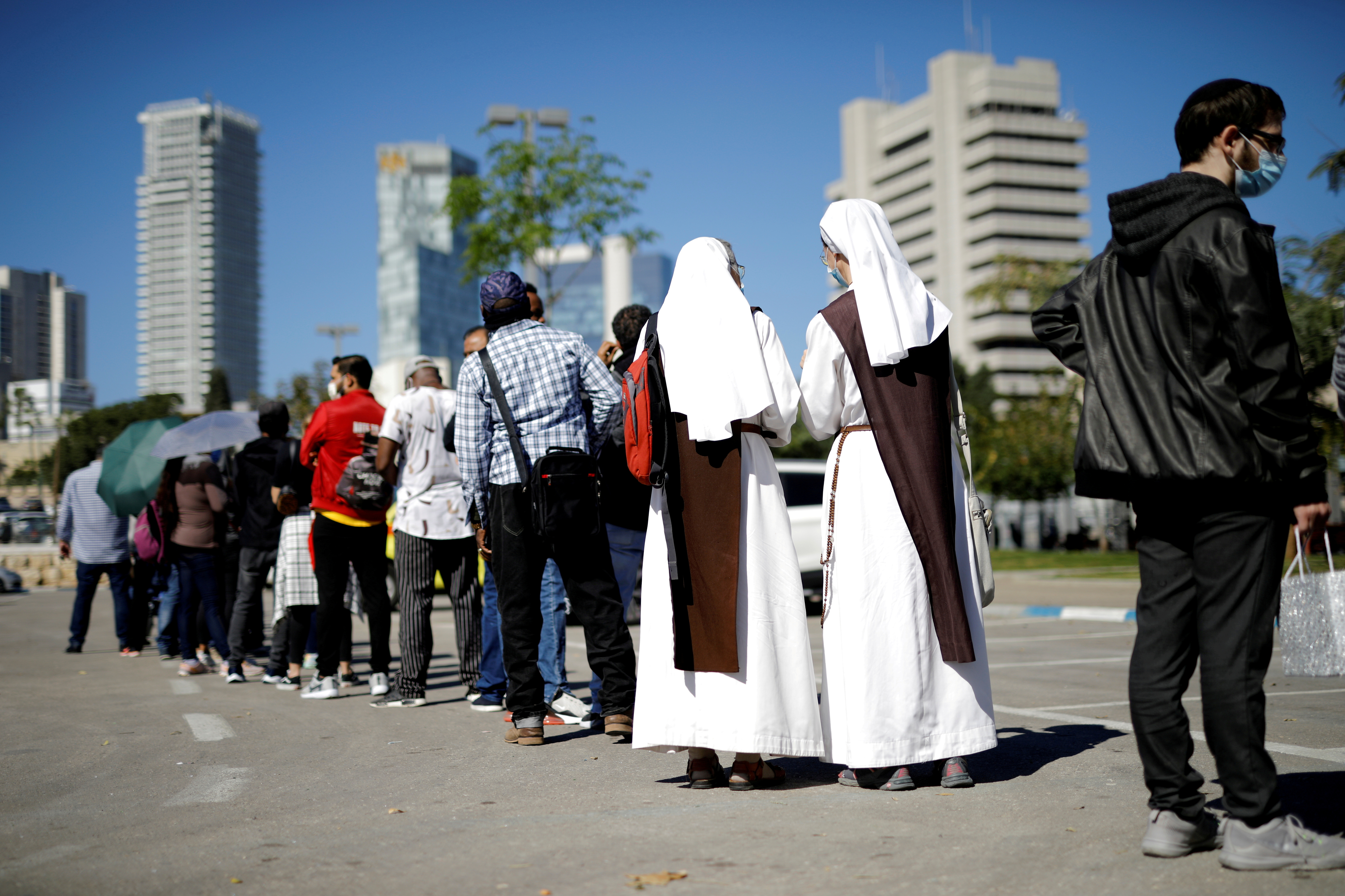Nuns stand in a queue outside a newly-opened centre administering vaccinations against the coronavirus disease (COVID-19) in a neighbourhood with a high residency of foreign nationals, including migrant workers, in Tel Aviv, Israel February 9, 2021. REUTERS/Amir Cohen/