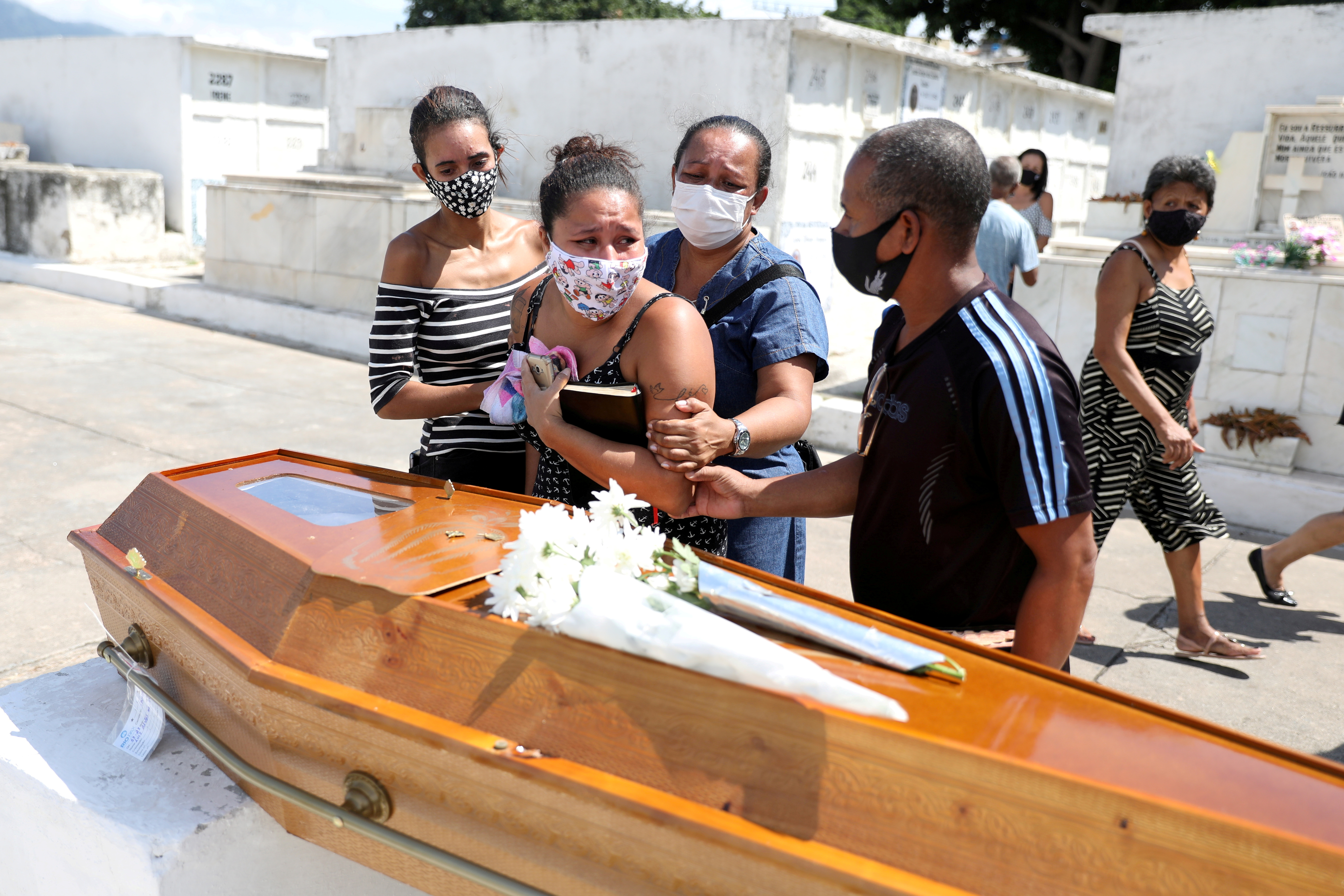 Relatives of Luiz Alves, 63, who died from coronavirus disease (COVID-19), react at his funeral at Inhauma cemetery in Rio de Janeiro, Brazil March 10, 2021. REUTERS/Pilar Olivares