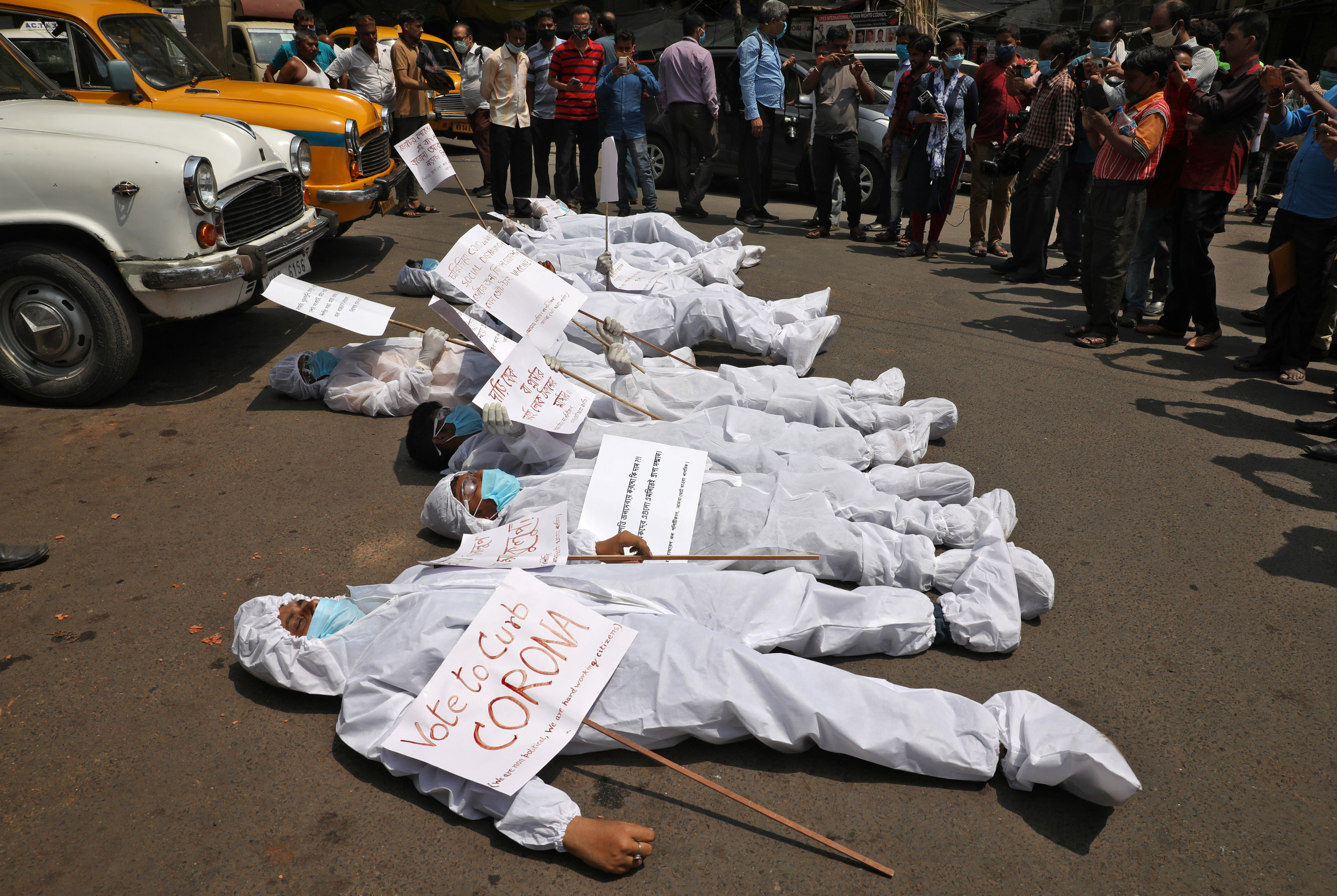 Demonstrators in protective suits and masks lie on a road during a protest demanding to stop election and campaign rallies in the eastern state of West Bengal, amidst the spread of the coronavirus disease (COVID-19), near the office of the Election Commission in Kolkata, India, April 7, 2021. REUTERS/Rupak De Chowdhuri/File Photo