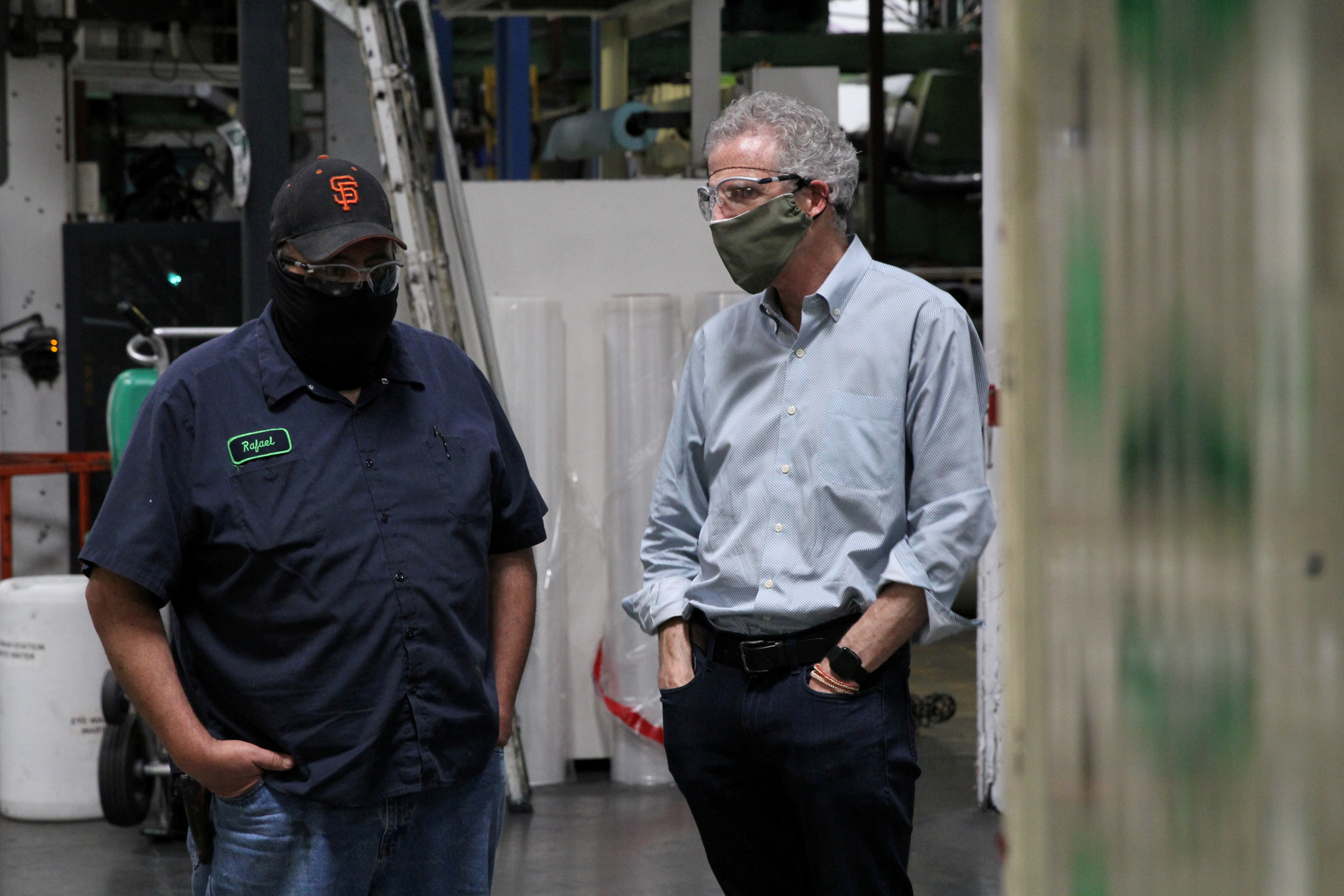 Kevin Kelly, CEO of Emerald Packaging, talks with an employee as they wear protective masks on a production floor of the company, which prints packaging material to be used for produce, amid the coronavirus disease (COVID-19) outbreak, in Union City, California, U.S. on May 7, 2020. REUTERS/Nathan Frandino/File Photo