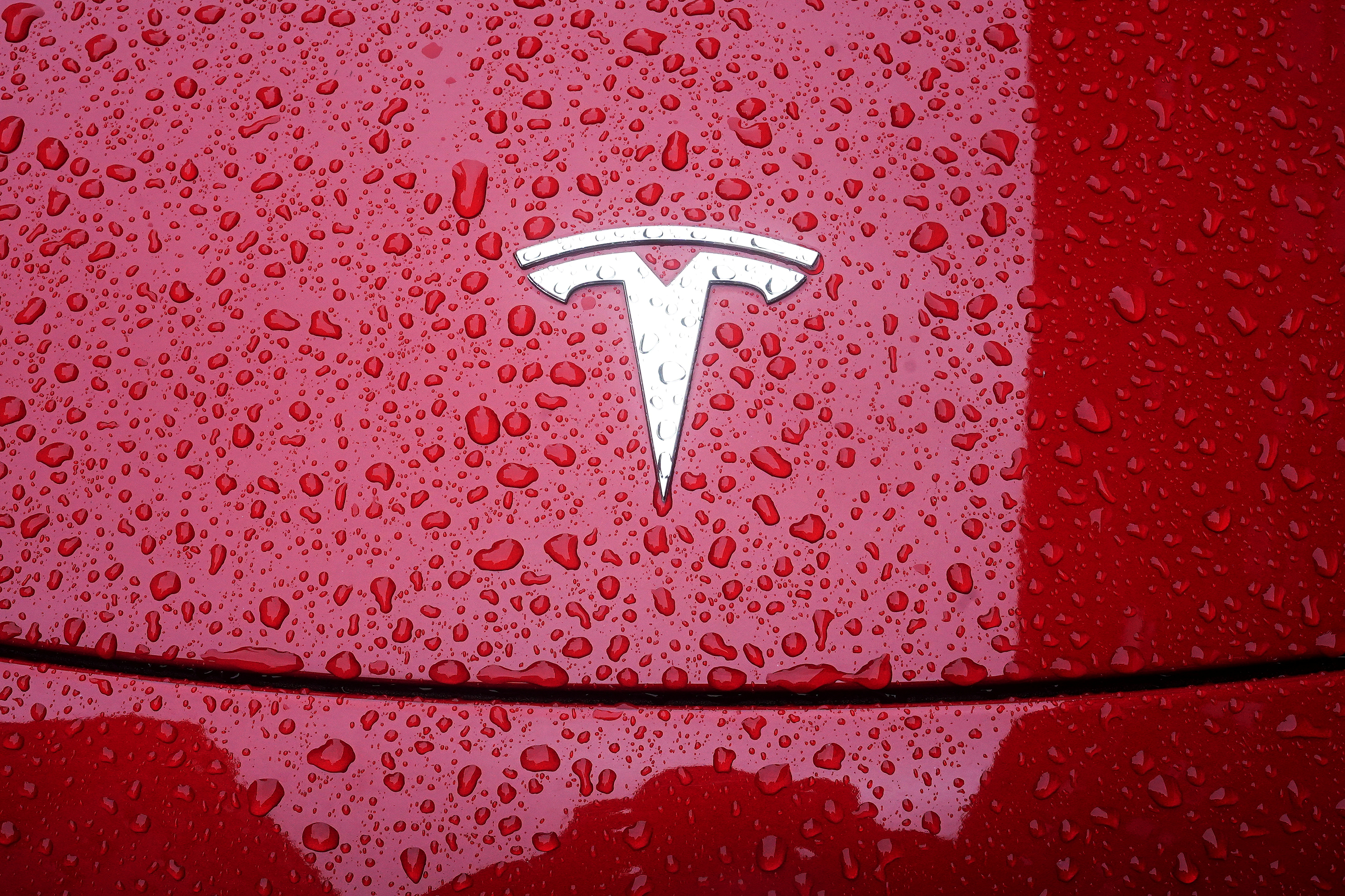 A Tesla logo is pictured on a car in the rain in the Manhattan borough of New York City, New York, U.S., May 5, 2021. REUTERS/Carlo Allegri/File Photo