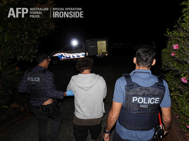 A person is detained by Australian Federal Police after its Operation Ironside against organised crime in this undated handout photo released June 8, 2021.   Australian Federal Police/Handout via REUTERS