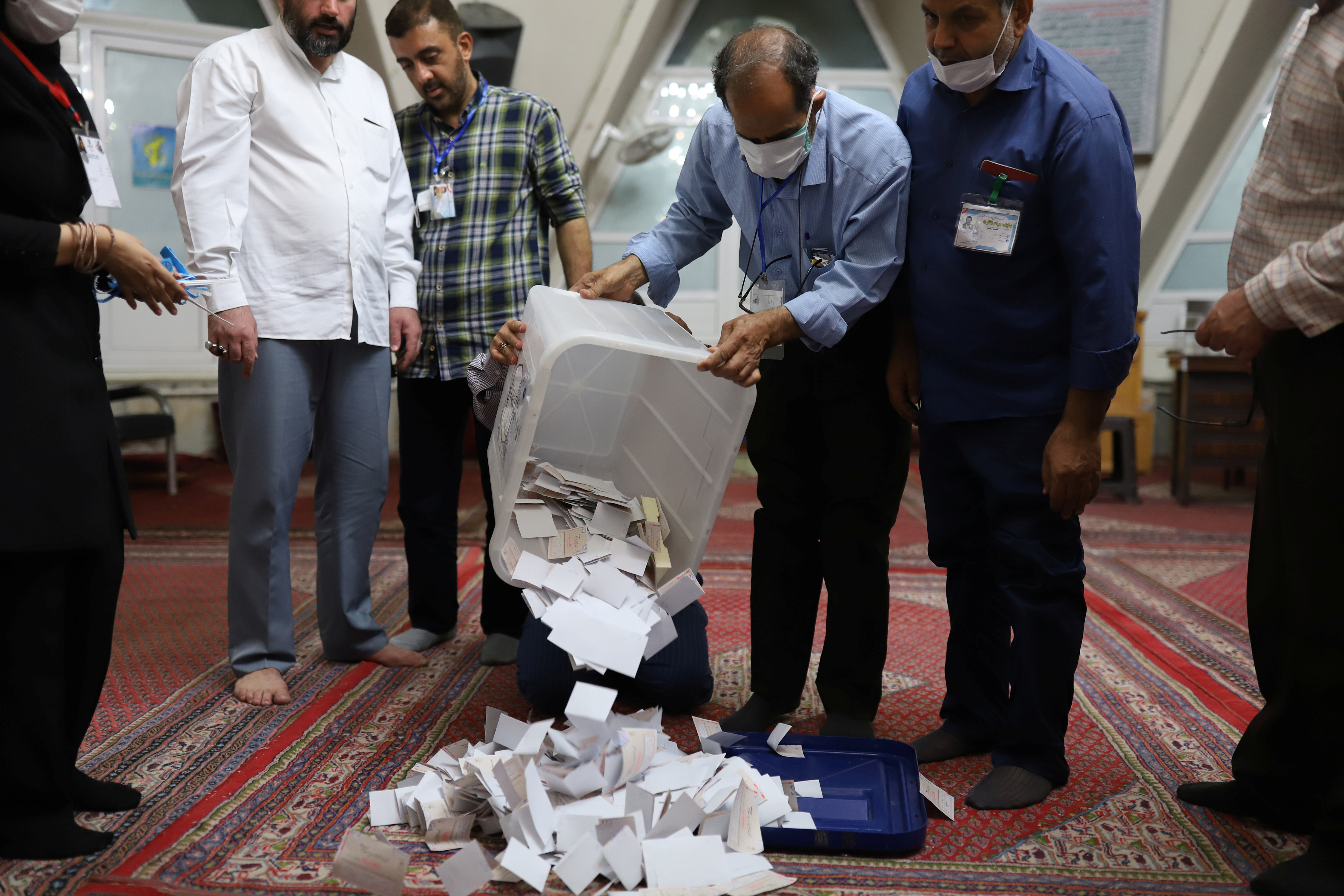 An electoral staff empties full ballot boxes after voting ended in the presidential election in Tehran, Iran June 19, 2021. Majid Asgaripour/WANA (West Asia News Agency) via REUTERS
