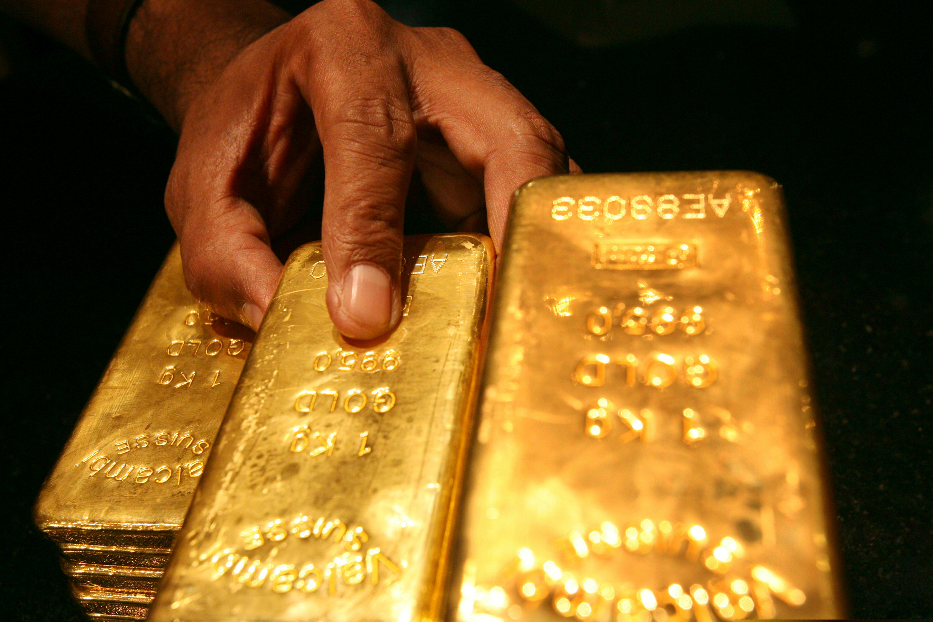 A security guard places several one kilo gold bars inside a secured vault in Dubai April 20, 2006.