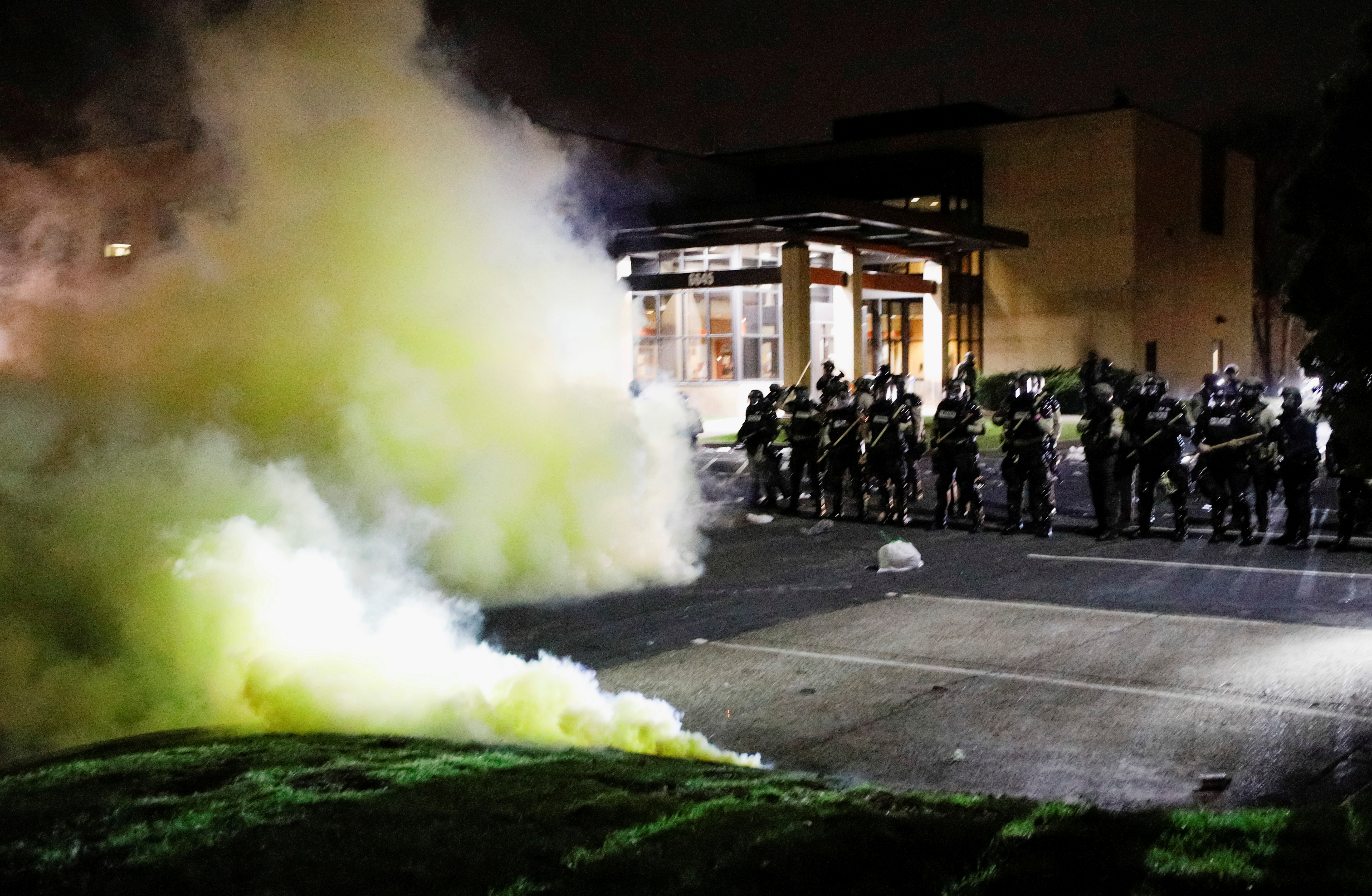 Tear gas is seen as officers stand guard outside Brooklyn Center Police Department with trash thrown at them by demonstrators at their feet after police allegedly shot and killed a man, who local media report is identified by the victim's mother as Daunte Wright, in Brooklyn Center, Minnesota, U.S., April 11, 2021. REUTERS/Nick Pfosi