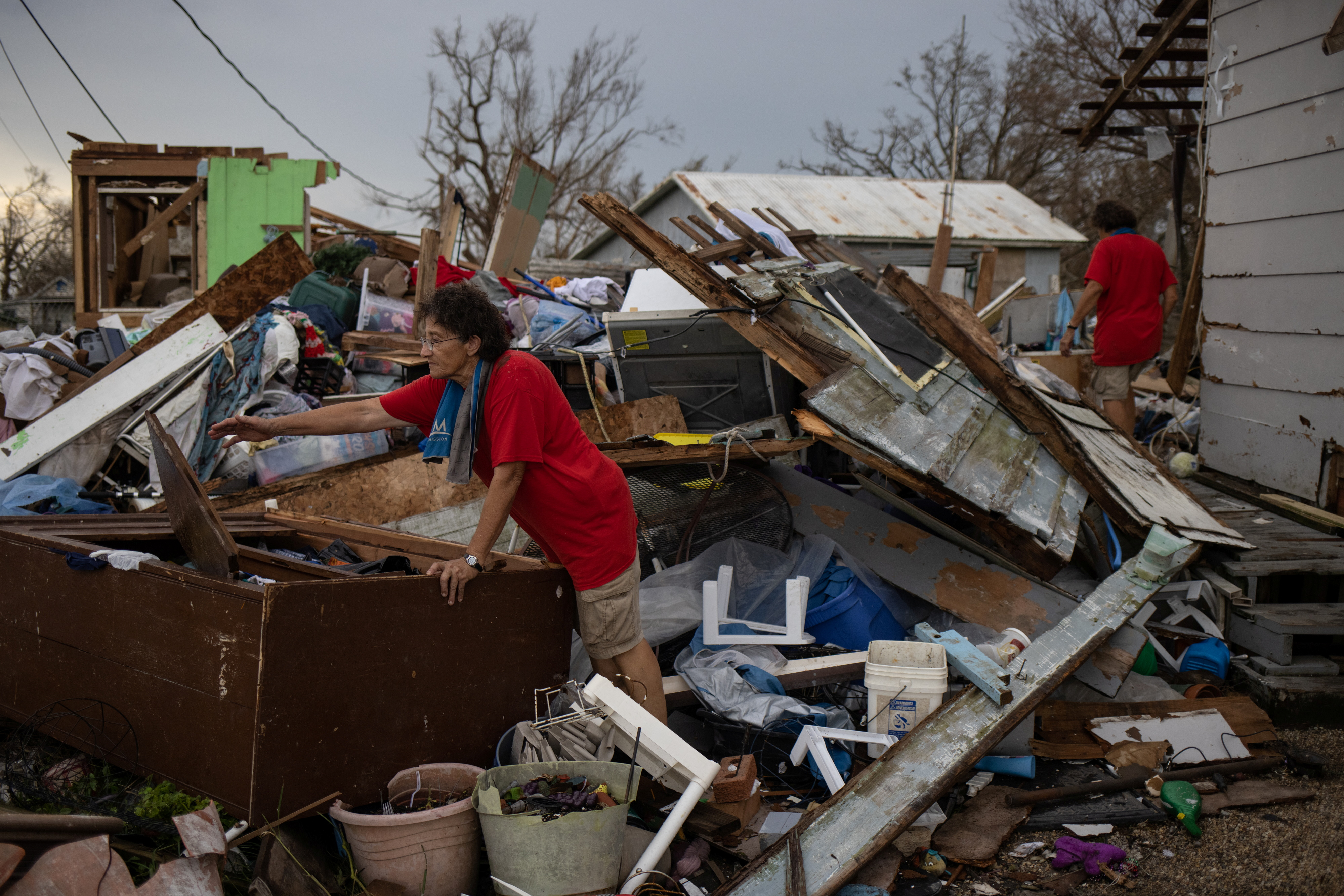 Twin sisters Bridget and Rosalie Serigny, 66, search for personal items stored in their shed which was left destroyed in the aftermath of Hurricane Ida in Golden Meadow, Louisiana, U.S., September 1, 2021.  REUTERS/Adrees Latif