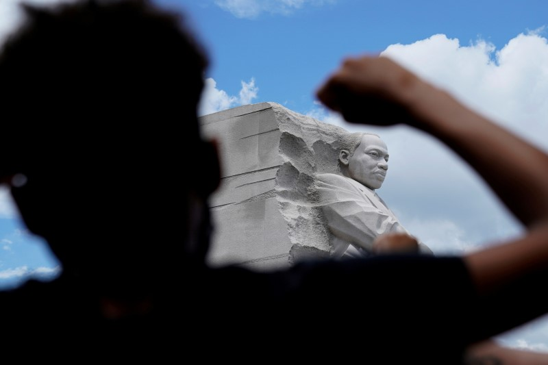 A demonstrator raises a fist in front of Martin Luther King Jr. Memorial during a protest to mark Juneteenth, which commemorates the end of slavery in Texas, two years after the 1863 Emancipation Proclamation freed slaves elsewhere in the United States, amid nationwide protests against racial inequality, in Washington, D.C., U.S., June 19, 2020. REUTERS/Erin Scott/File Photo