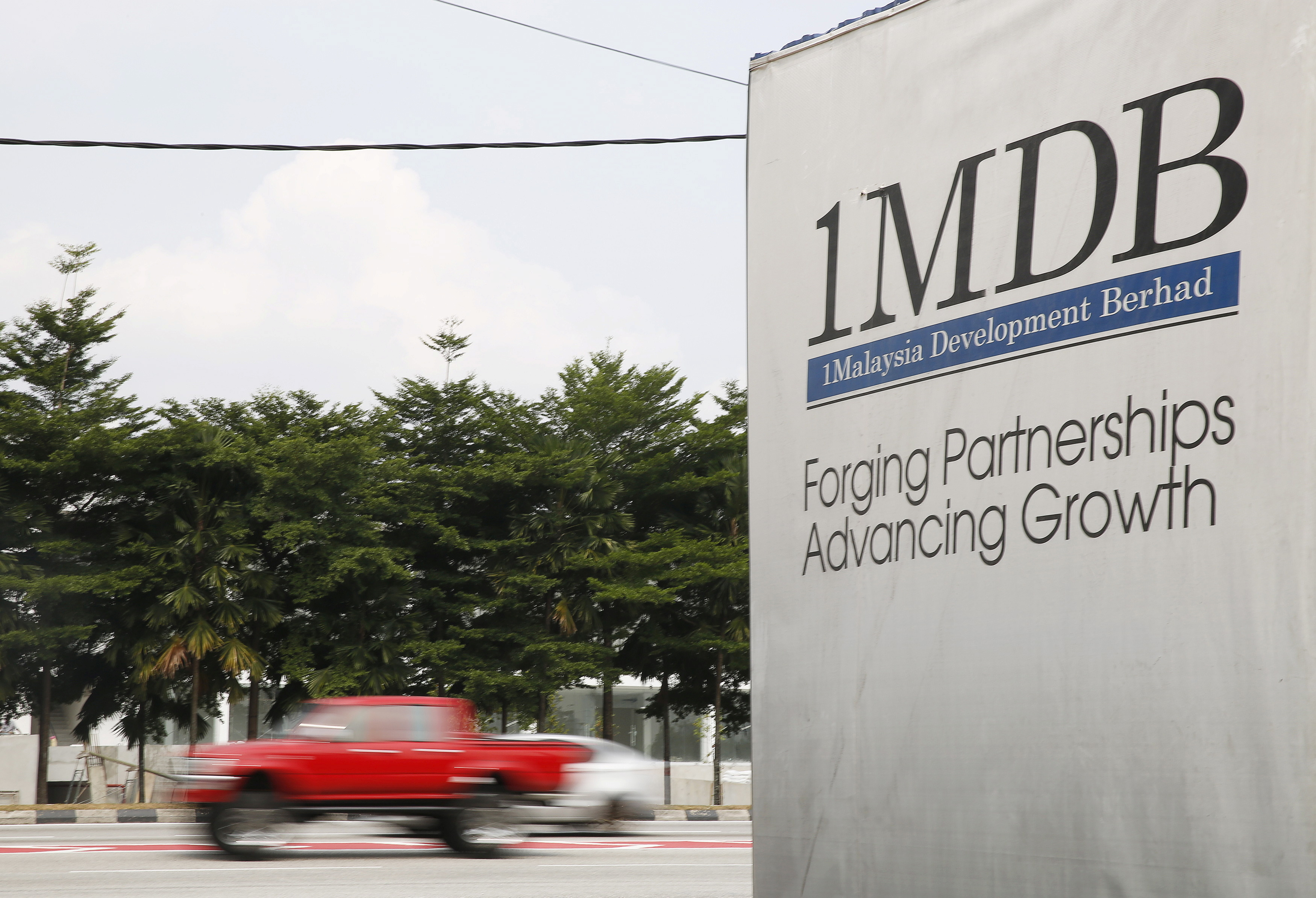 Traffic passes a 1Malaysia Development Berhad (1MDB) billboard at the Tun Razak Exchange development in Kuala Lumpur, Malaysia, July 6, 2015.REUTERS/Olivia Harris