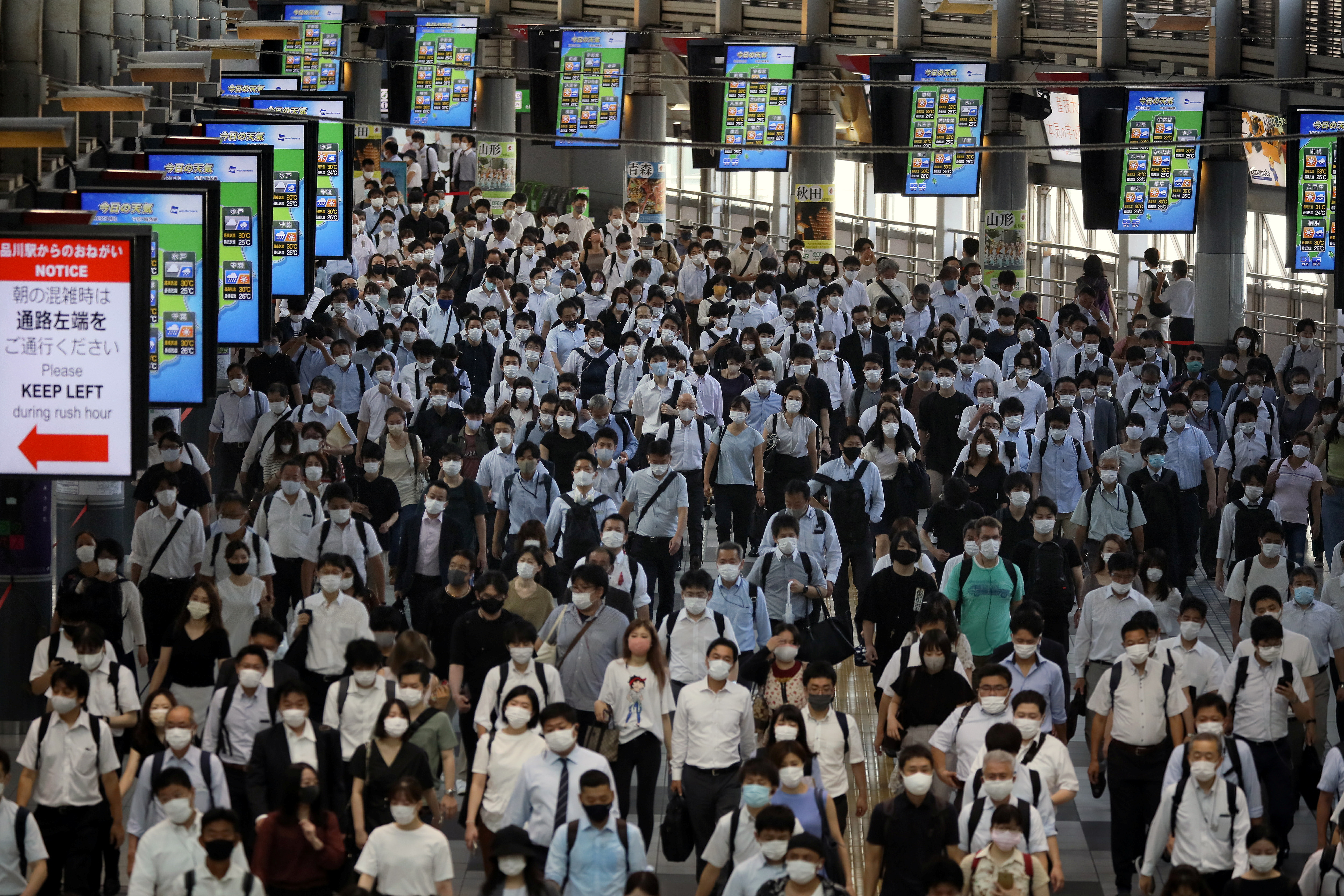 Commuters wearing face masks arrive at Shinagawa Station at the start of the working day amid the coronavirus disease (COVID-19) outbreak, in Tokyo, Japan, August 2, 2021.REUTERS/Kevin Coombs