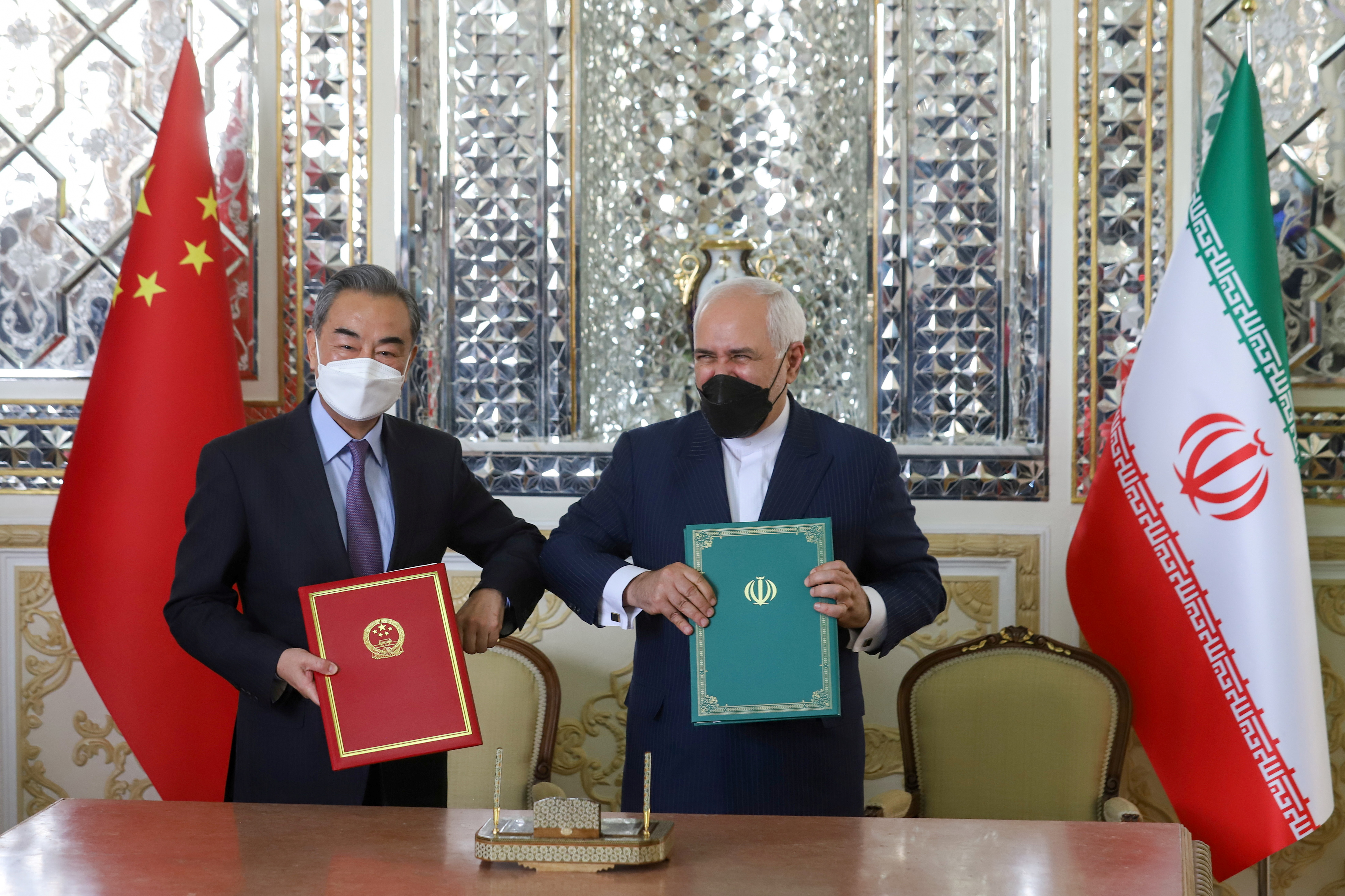 Iran's Foreign Minister Mohammad Javad Zarif and China's Foreign Minister Wang Yi bump elbows during the signing ceremony of a 25-year cooperation agreement, in Tehran, Iran March 27, 2021. Majid Asgaripour/WANA