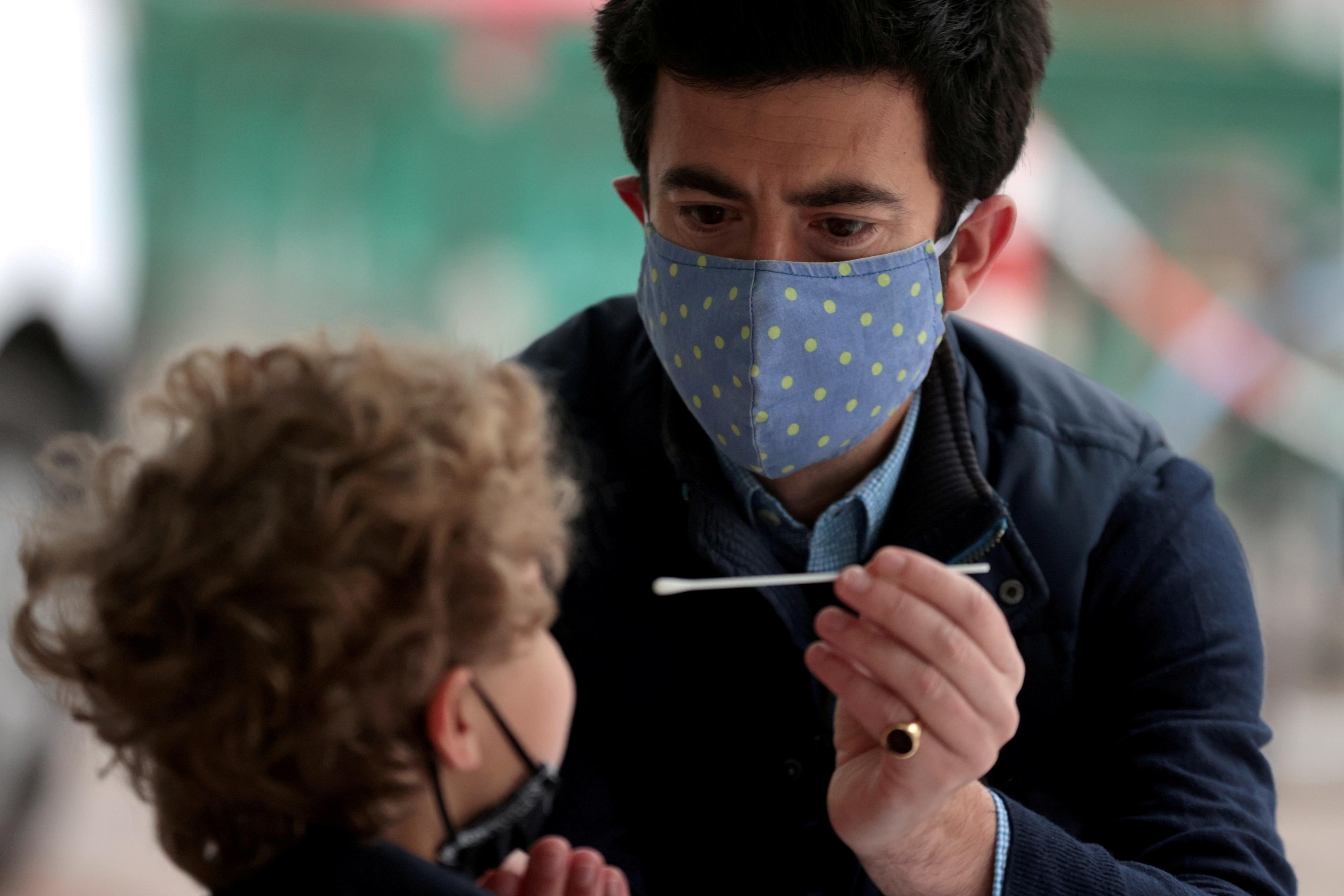 Мужчина берет мазок на коронавирусную болезнь (COVID-19) у своего сына на испытательном полигоне в Лондоне, Великобритания, 14 мая 2021 года. REUTERS/Ханна Маккей