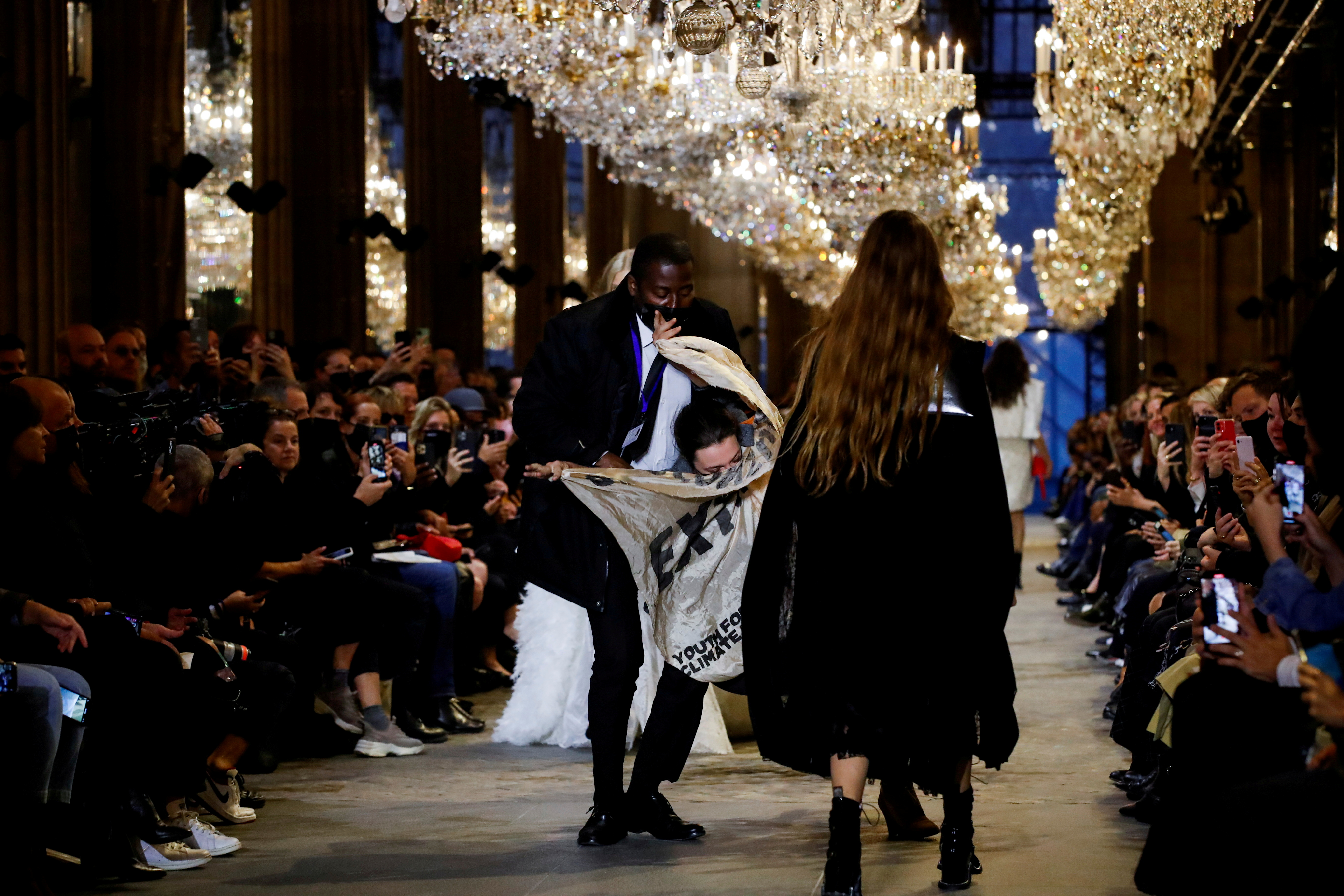 A member of the security personnel removes an activist belonging to the 'Les Amis de la Terre France' or 'Friends of the Earth - France' , who crashed the designer Nicolas Ghesquiere Spring/Summer 2022 women's ready-to-wear collection show for fashion house Louis Vuitton during Paris Fashion Week in Paris, France, October 5, 2021. REUTERS/Gonzalo Fuentes