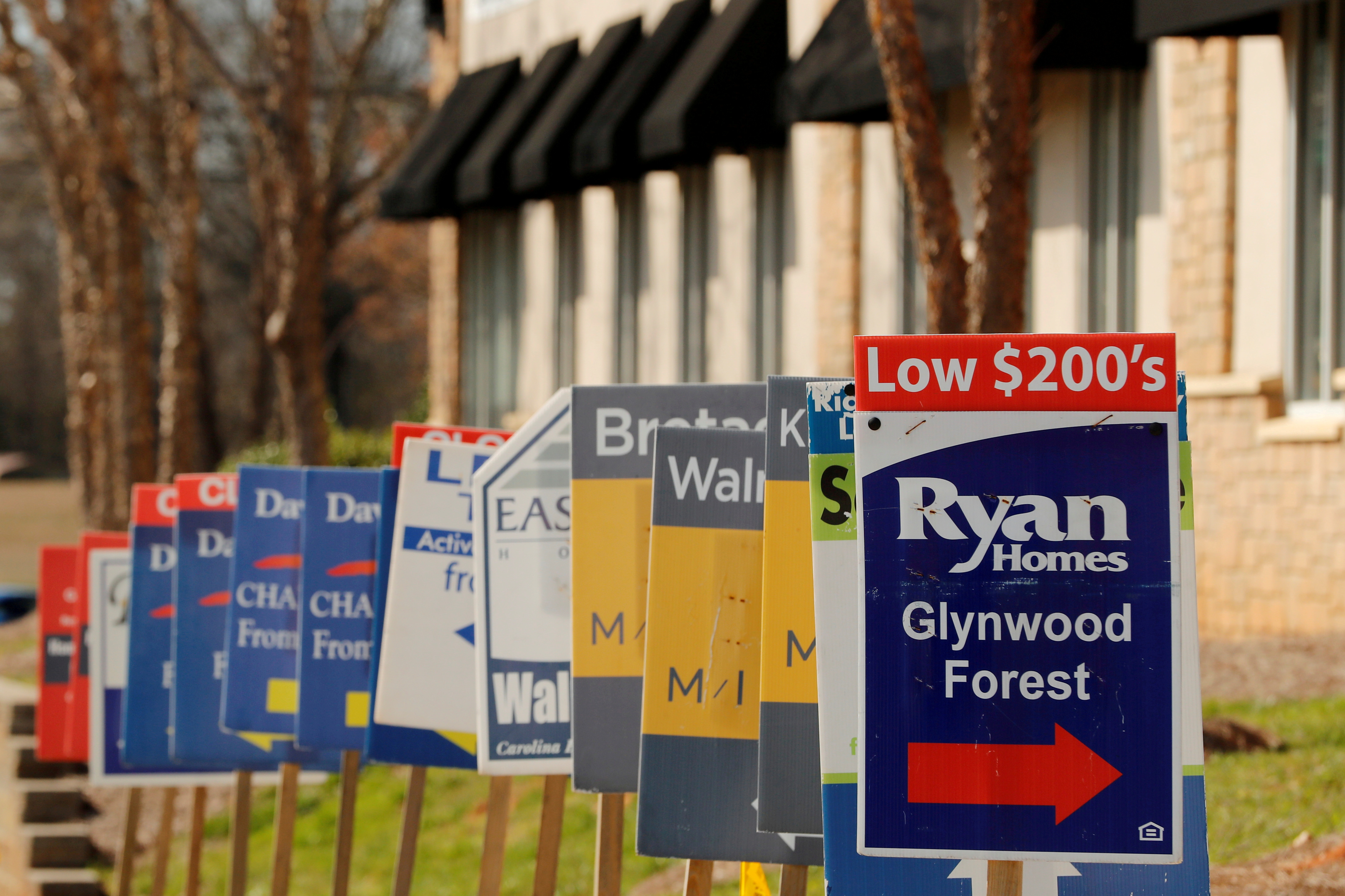 Real estate signs advertise new homes for sale in multiple new developments in York County, South Carolina, U.S., February 29, 2020. REUTERS/Lucas Jackson//File Photo